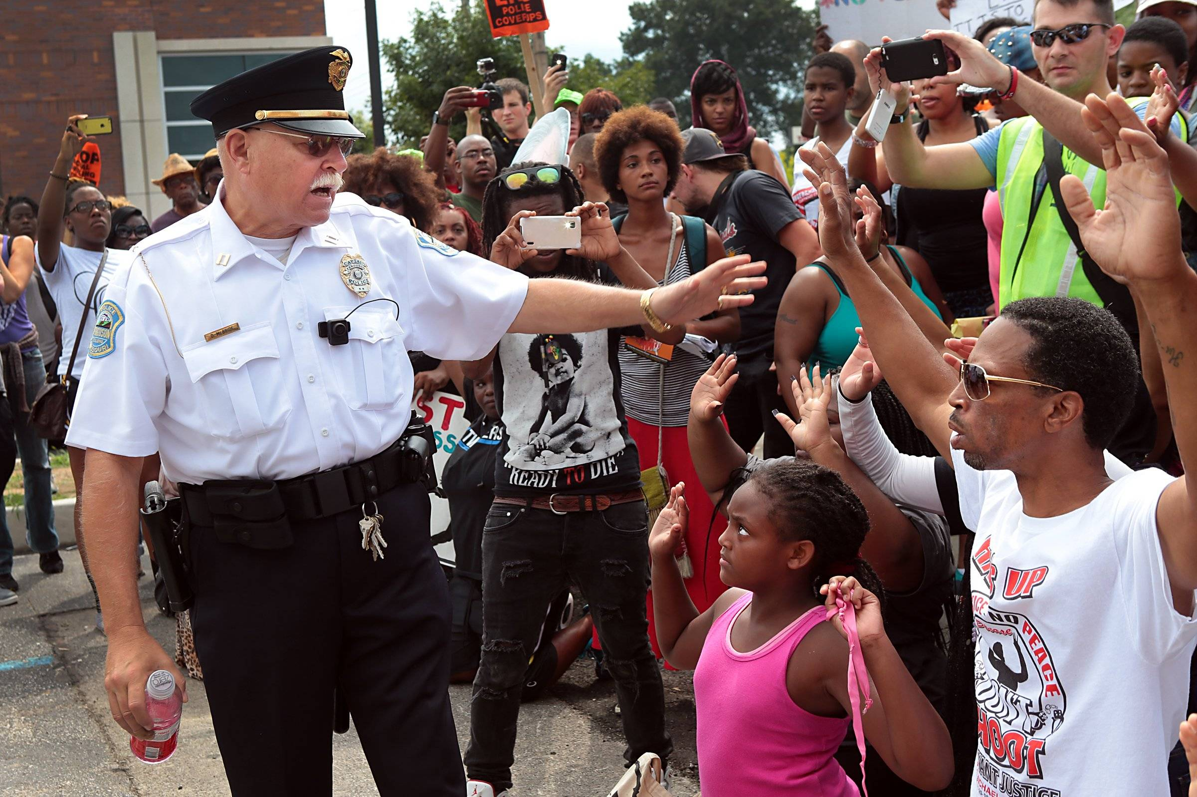 Ferguson Police Capt. D. McBride orders protesters back to the sidewalk at a demonstration in front of the police station in Ferguson, Mo., Aug. 30, for Michael Brown, an unarmed black 18-year-old who was fatally shot by a white police officer three weeks earlier. Protesters ignored his order, instead moving further up the driveway.