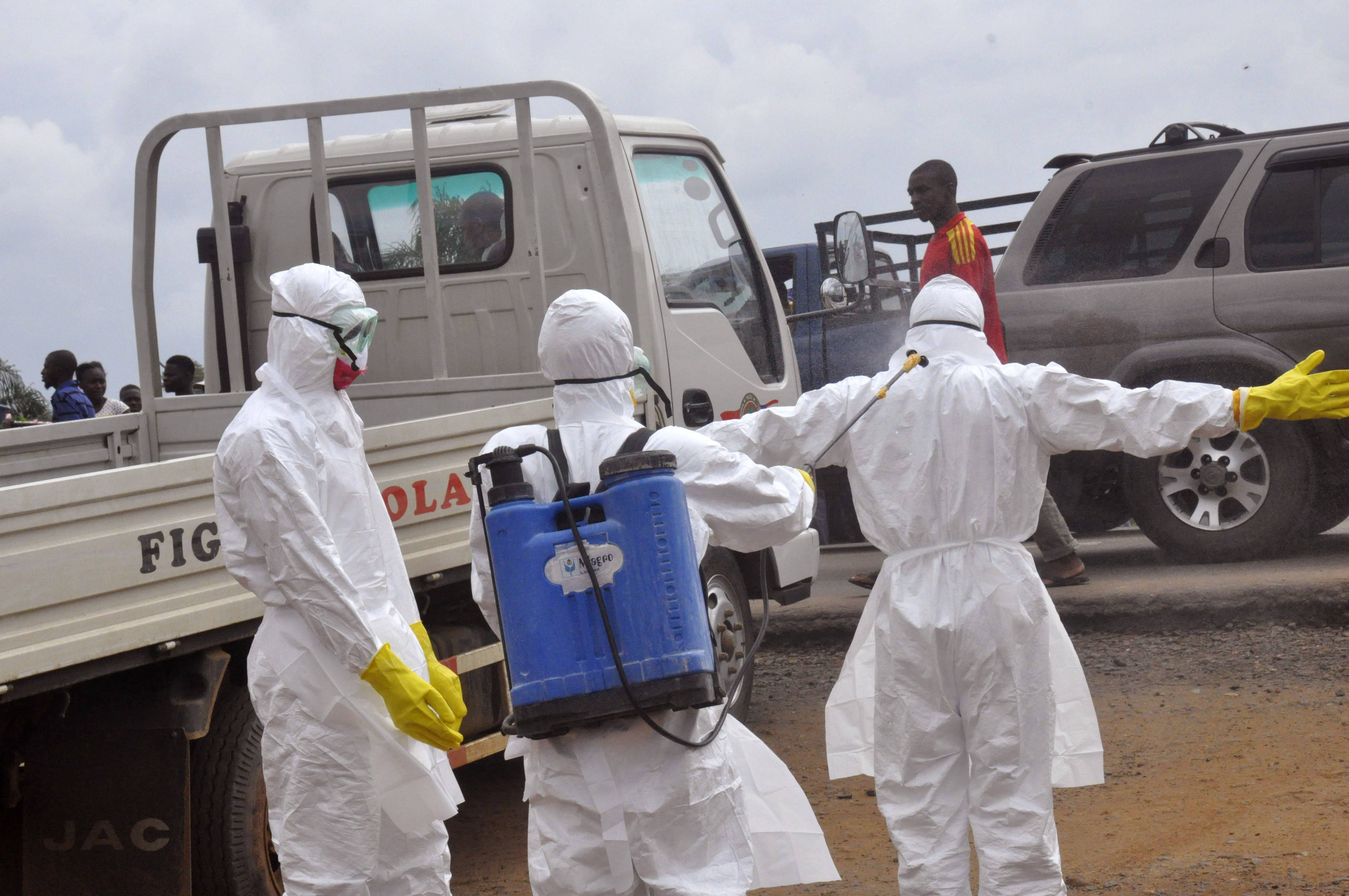Health worker's spray each other with disinfectant chemicals after they worked with a suspected Ebola virus death in Monrovia, Liberia, Thursday.