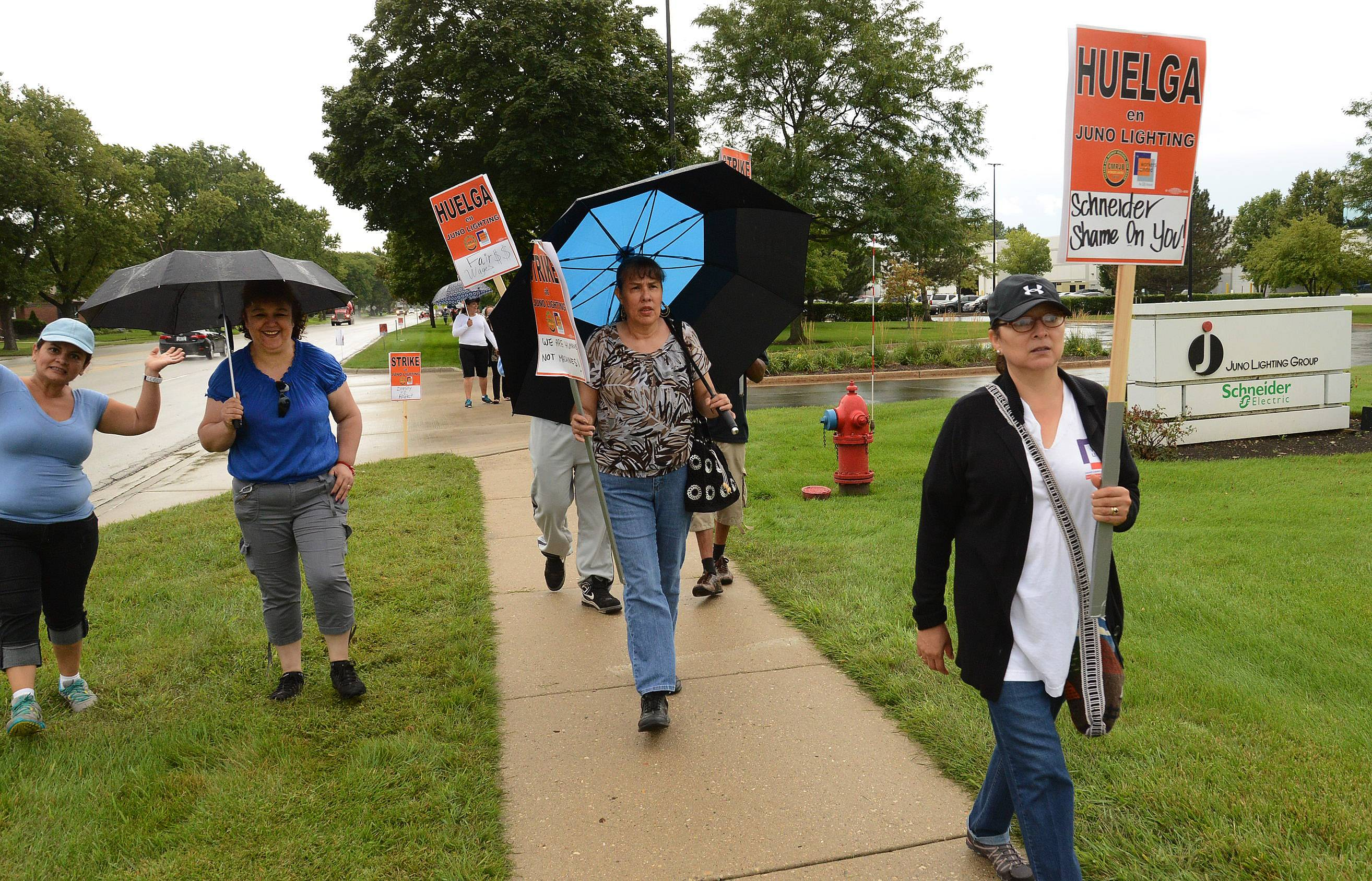 Workers picket in occasional rain Thursday outside Juno Lighting Group in Des Plaines. Almost 400 workers went on strike Wednesday, calling for higher wages.