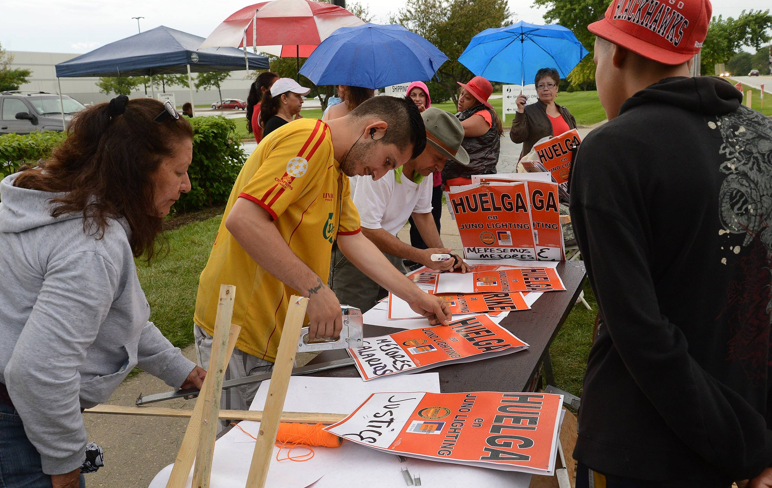 Workers make picket signs Thursday outside Juno Lighting Group in Des Plaines during the second day of their strike.