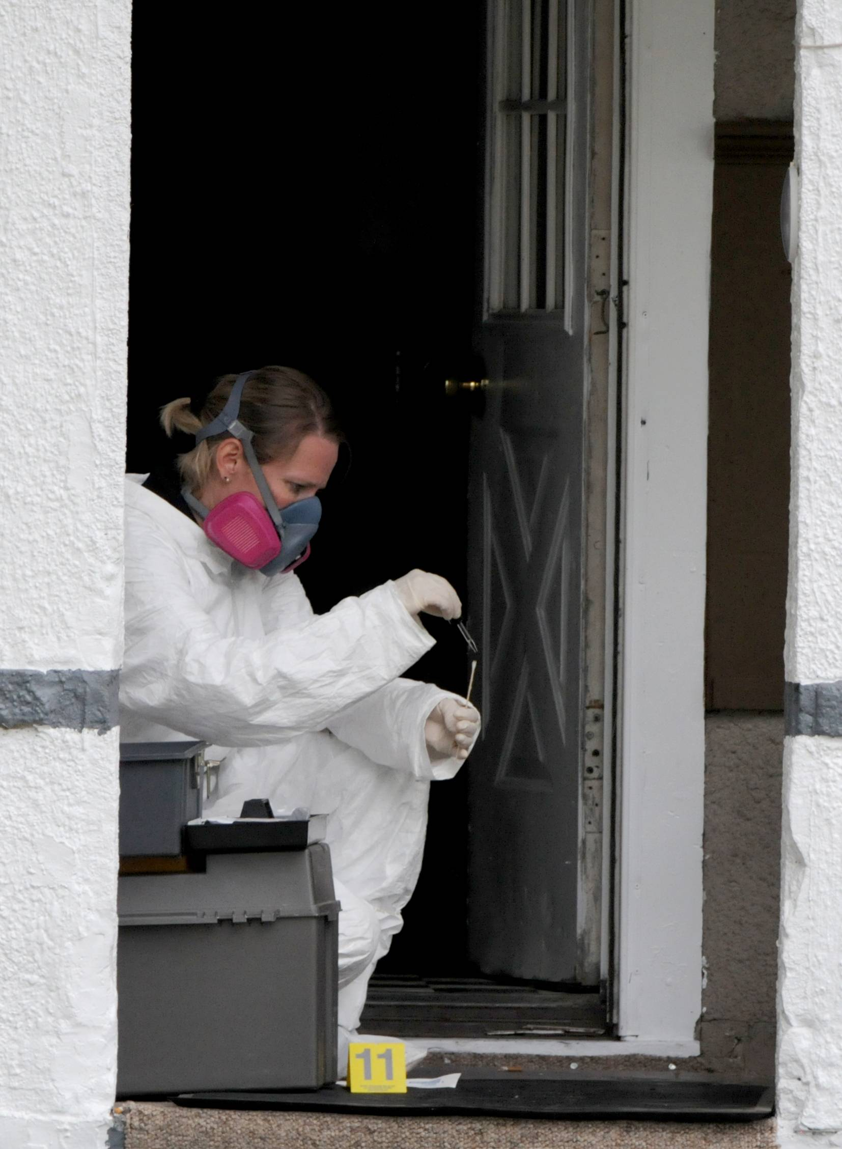 Brenda McNeely collects evidence at a home in Bucyrus, Ohio, where one of four men were found beaten to death Monday.