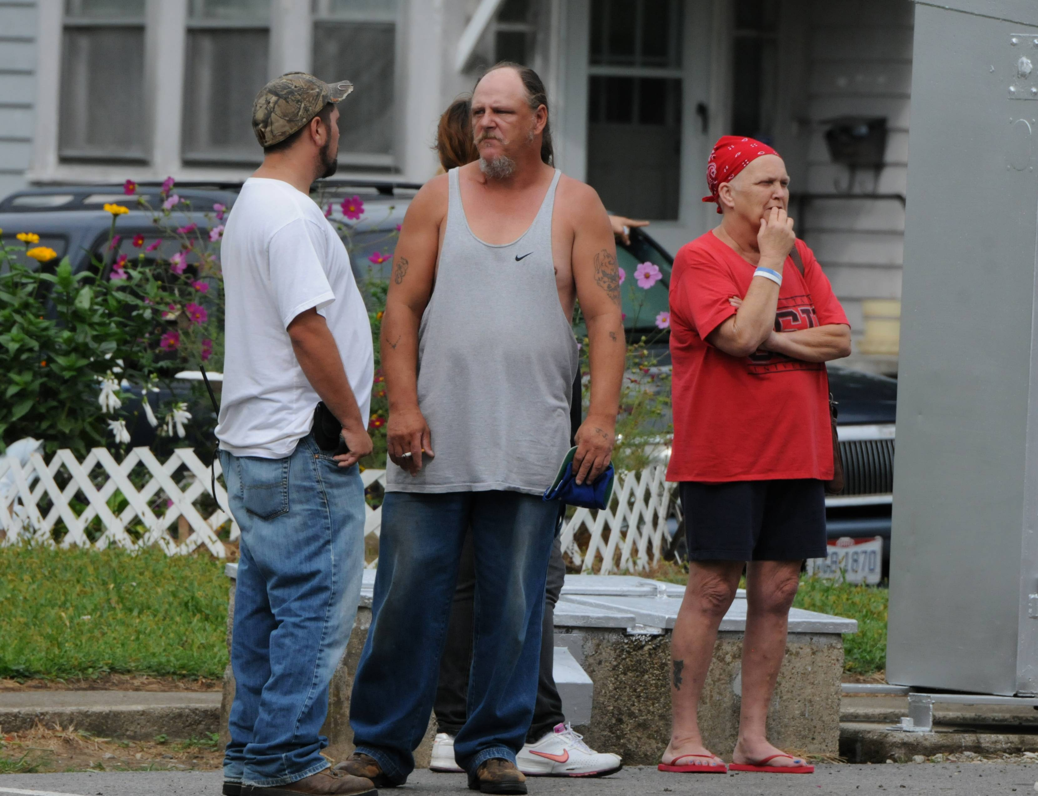 Residents look on as police investigate a home in Bucyrus, Ohio, where one of four men were found beaten to death Monday.