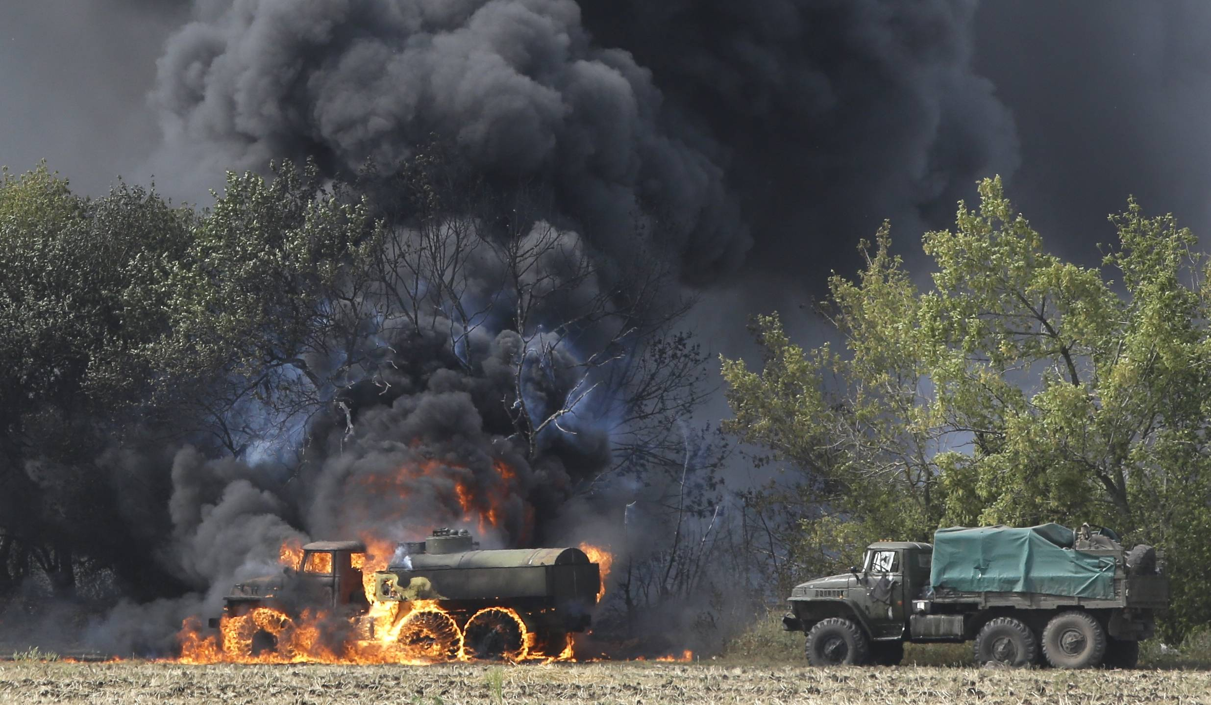 Unmarked Military vehicles burn near the village of Berezove, eastern Ukraine, Thursday, after a clash between pro-government troops and Russian-backed separatist militia. Separatist rebels have made major strides in their offensive against Ukrainian government forces in recent days, drawing on what Ukraine and NATO says is ample support from the Russian military.