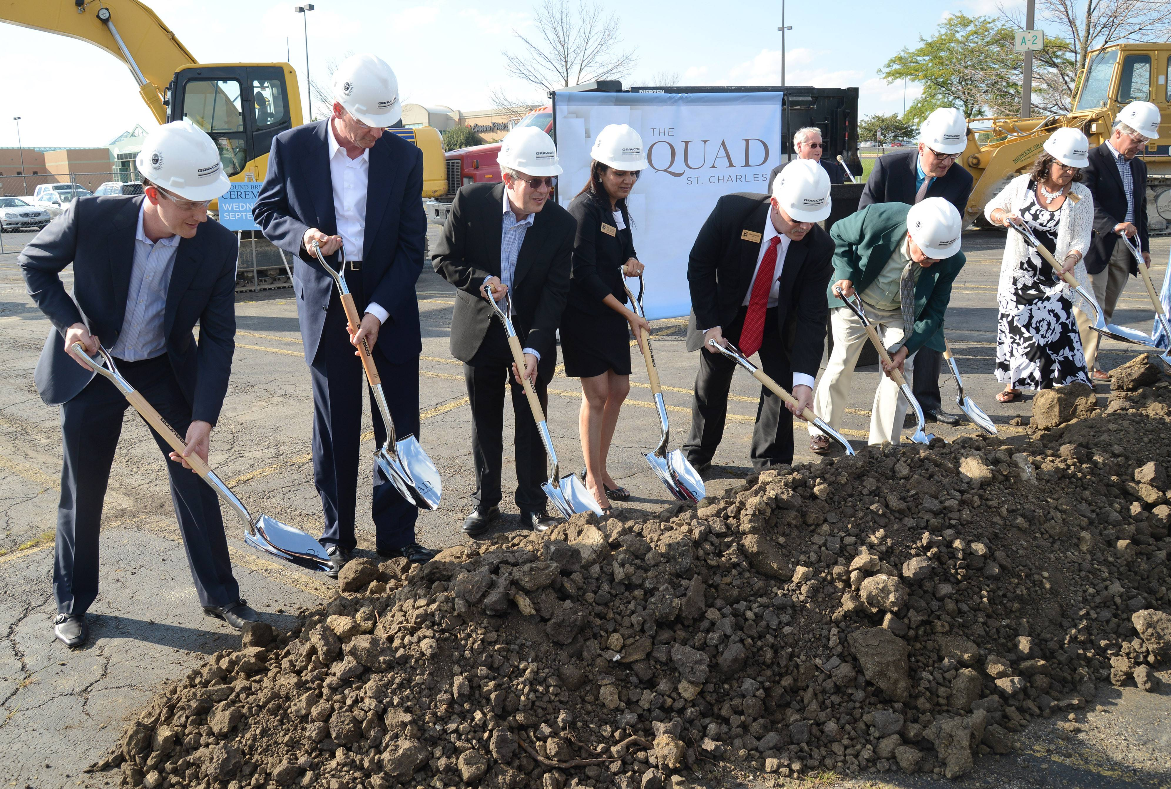 City aldermen and St. Charles Mayor Ray Rogina, third from right, throw ceremonial dirt at the groundbreaking ceremony for The Quad in St. Charles on Wednesday.