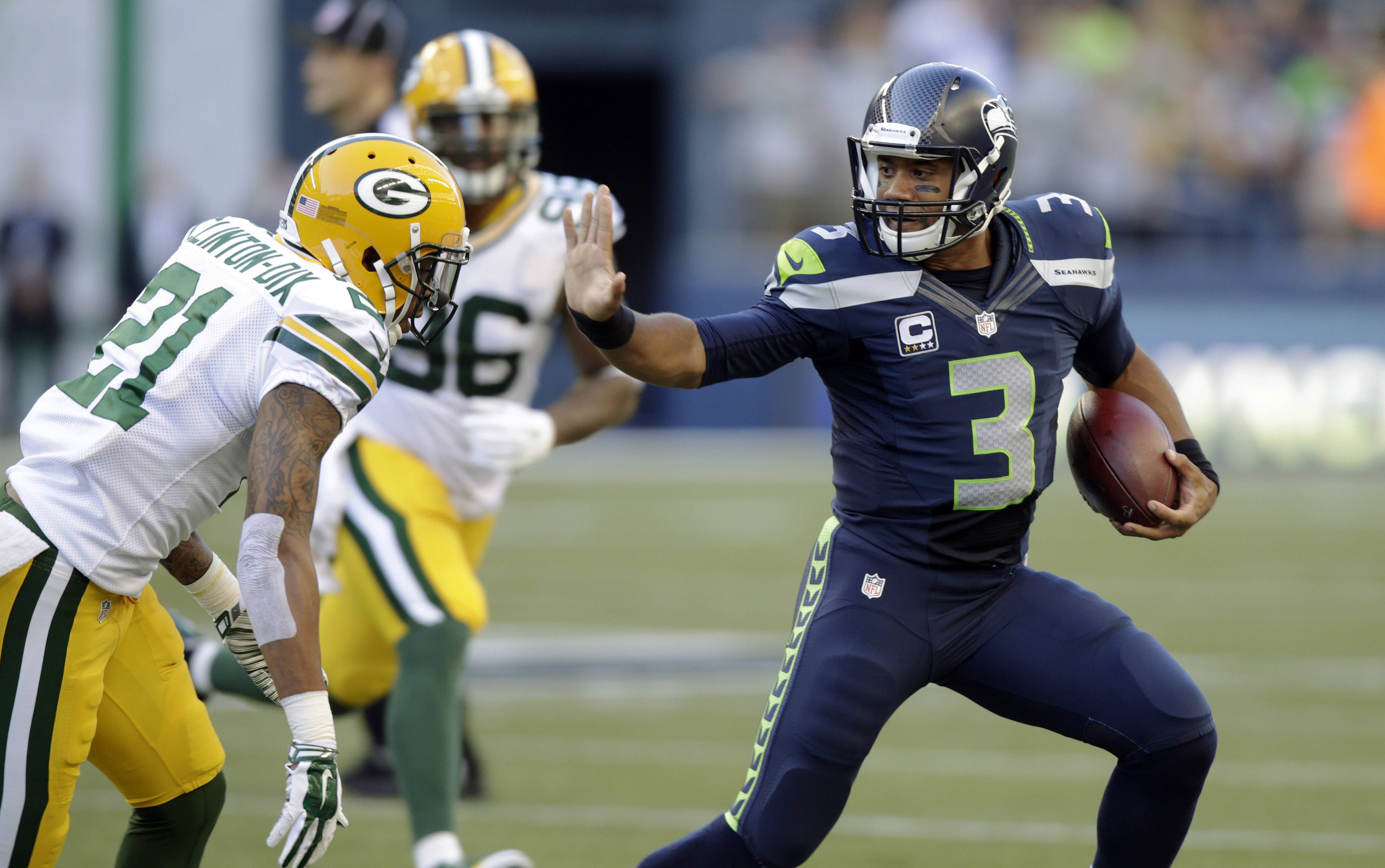 Seattle Seahawks quarterback Russell Wilson (3) avoids Green Bay Packers' Ha Ha Clinton-Dix (21) during the first half of an NFL football game, Thursday, Sept. 4, 2014, in Seattle.