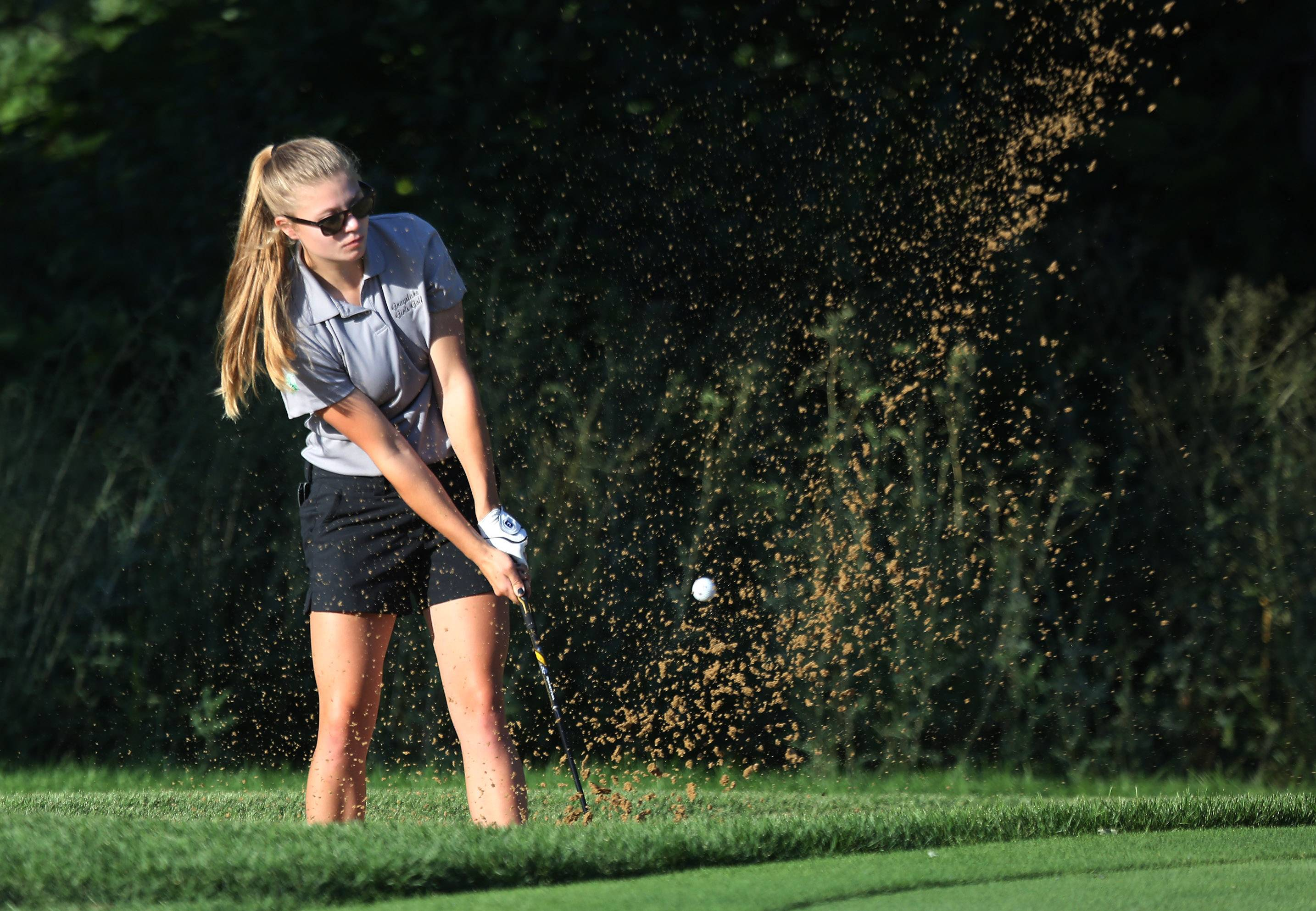 Grayslake golfer Kim Balling hits out of a sand trap on the 9th hole during the match between Grayslake and Marengo on Thursday at Brae Loch Golf Course in Grayslake.
