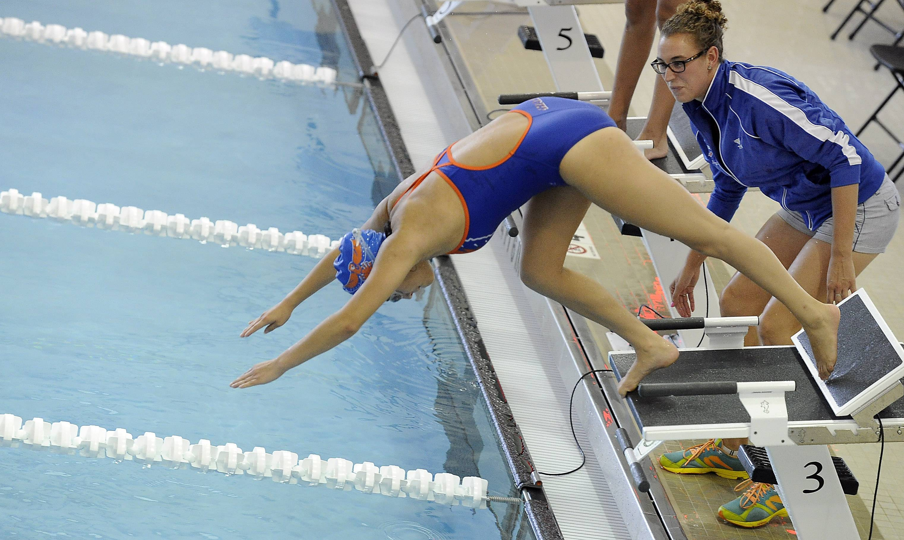 The new pool at Buffalo Grove High School has Kiefer starting blocks which allow for track-style starts. Here, Hoffman Estates assistant coach Jenny Toler helps an athlete with technique.