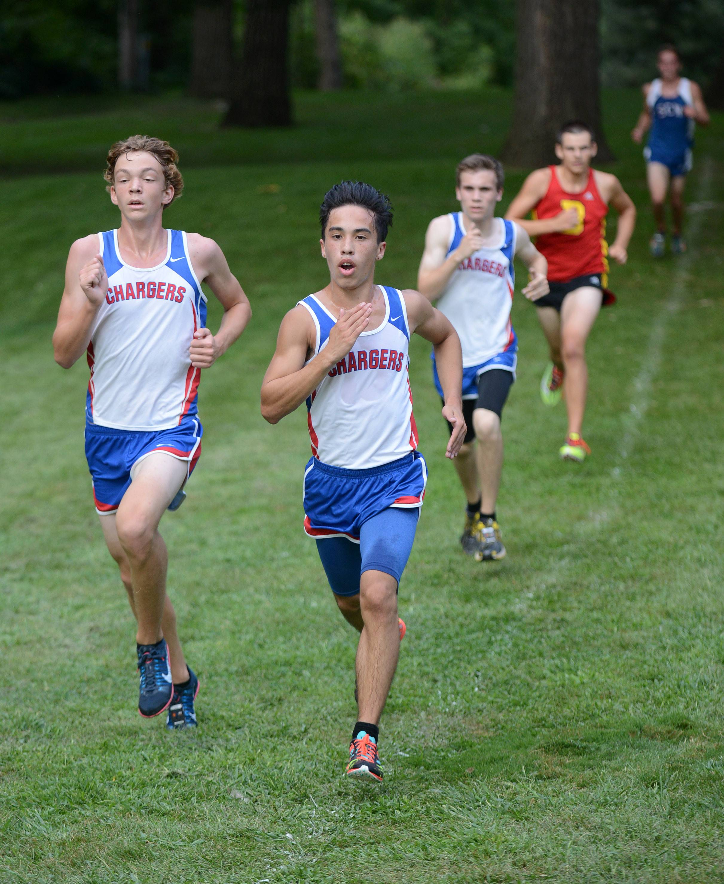 Dundee-Crown's Alex Clark, left, and Ricky Nueve run side-by-side nearing the final leg of the varsity run at the Elgin Invite cross country meet at Lords Park in Elgin on Tuesday.