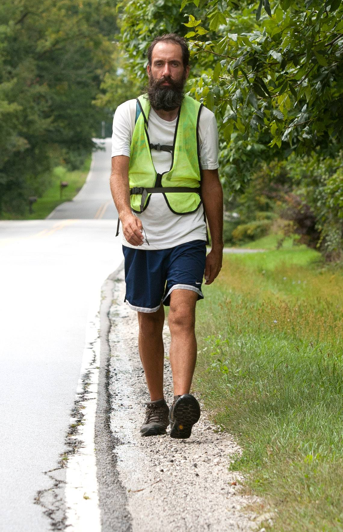 Jeffrey Czerwiec of Des Moines, Iowa, walks down Mack Road in Warrenville Thursday. He is one of three dozen activists taking part in a cross-country trek from Los Angeles to Washington D.C. called the Great March for Climate Action.