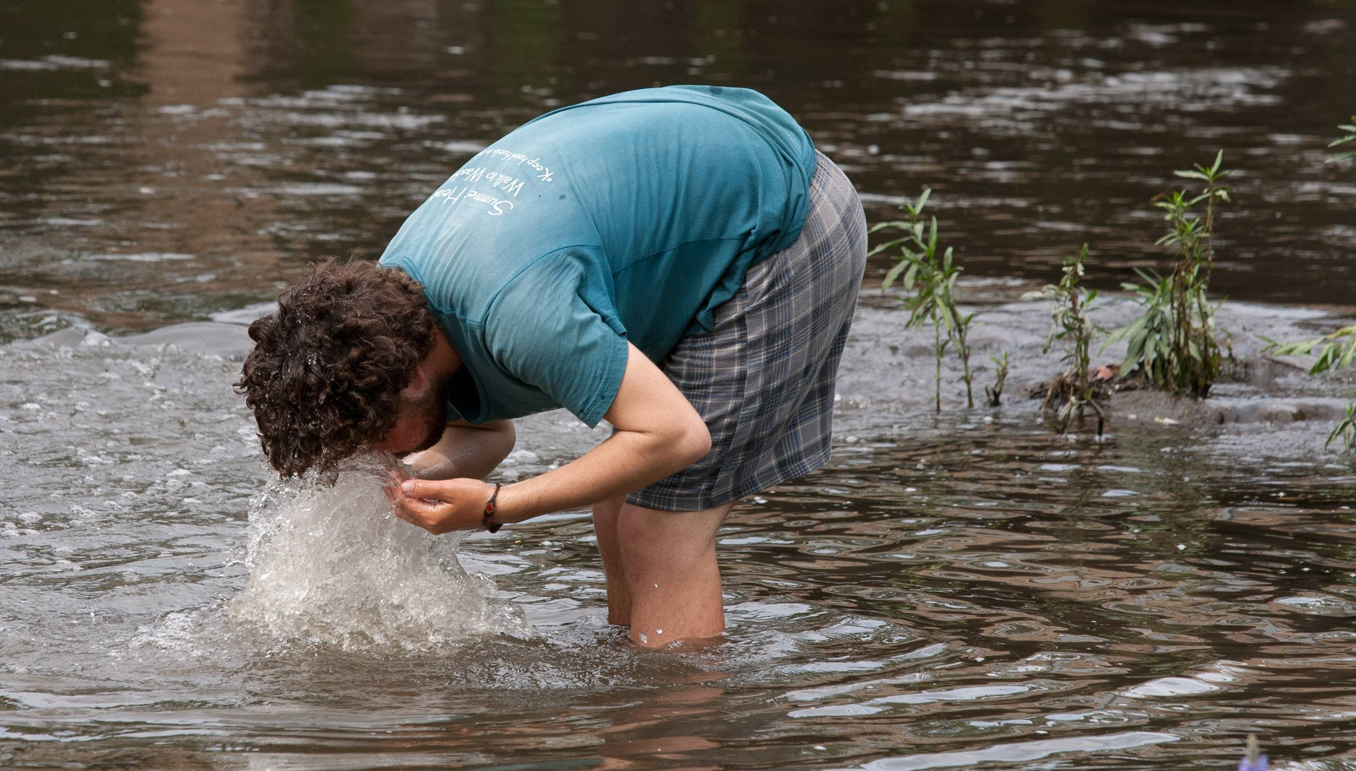 Benjamin Bushwick of Rockville, Md. refreshes himself in the west branch of the DuPage River in Warrenville Thursday. He is one of about three dozen activists traveling on foot from Los Angeles to Washington D.C. as part of the Great March for Climate Action.