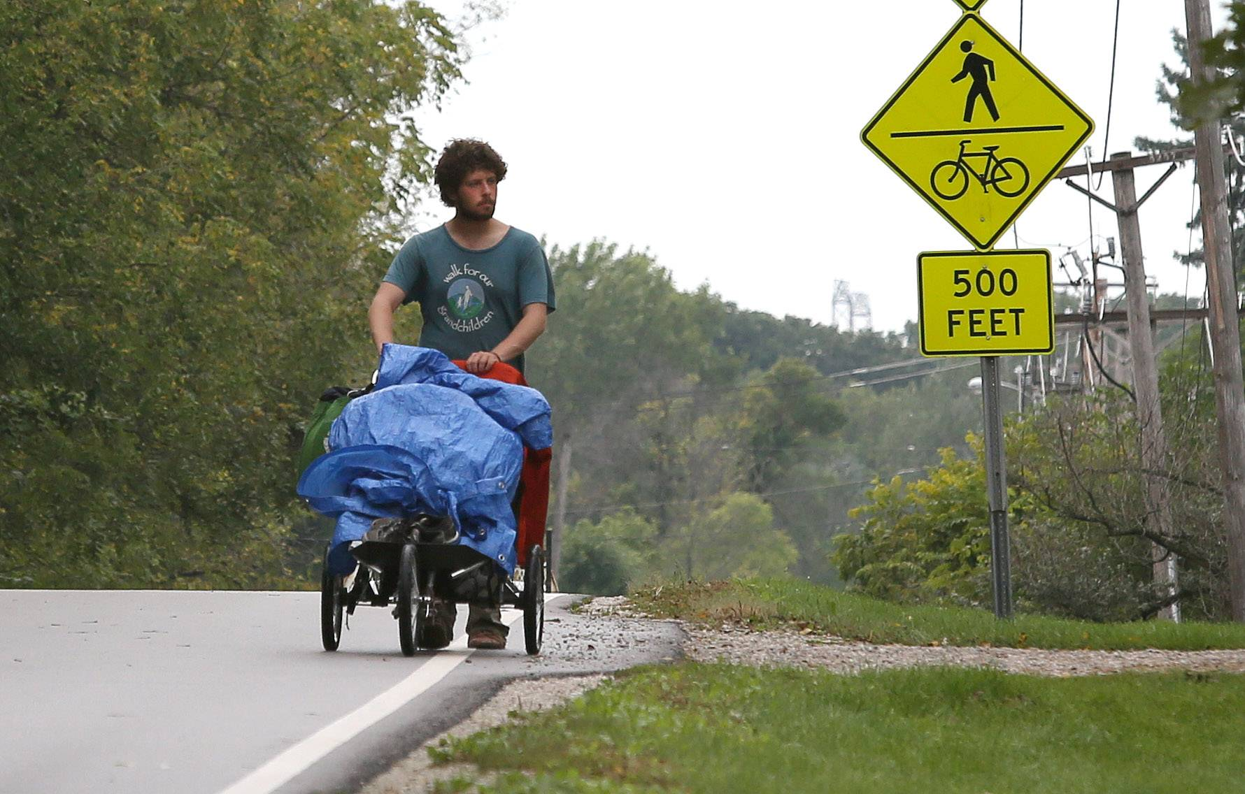 Benjamin Bushwick of Rockville, Md., walks down Mack Road in Warrenville Thursday. He is one of three dozen activists taking part in a cross-country trek from Los Angeles to Washington D.C. called the Great March for Climate Action.