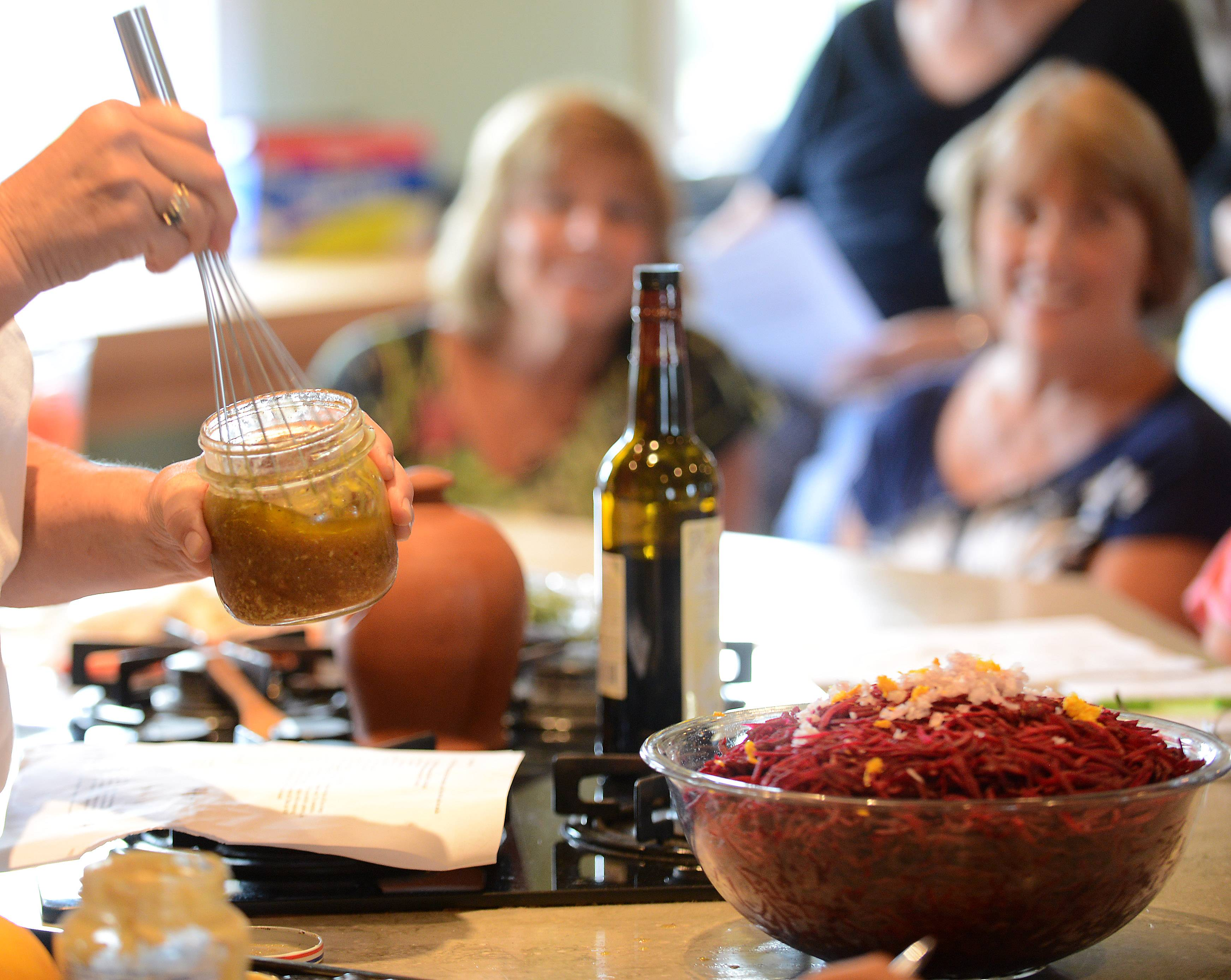 Penny Newkirk of Country Garden Cuisine whisks a vinaigrette for a beet salad during a class of around 20 students.