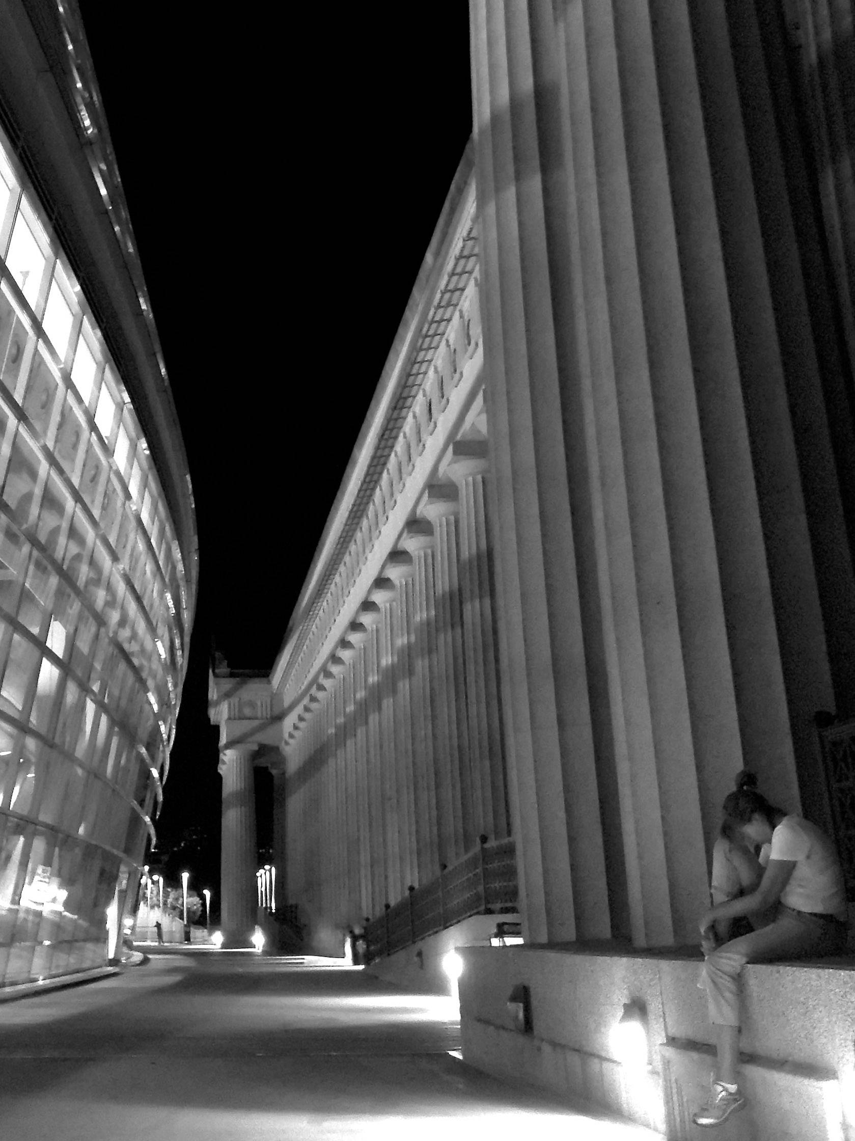 A solemn woman sits on the steps at night outside Soldier Field in Chicago after a concert.