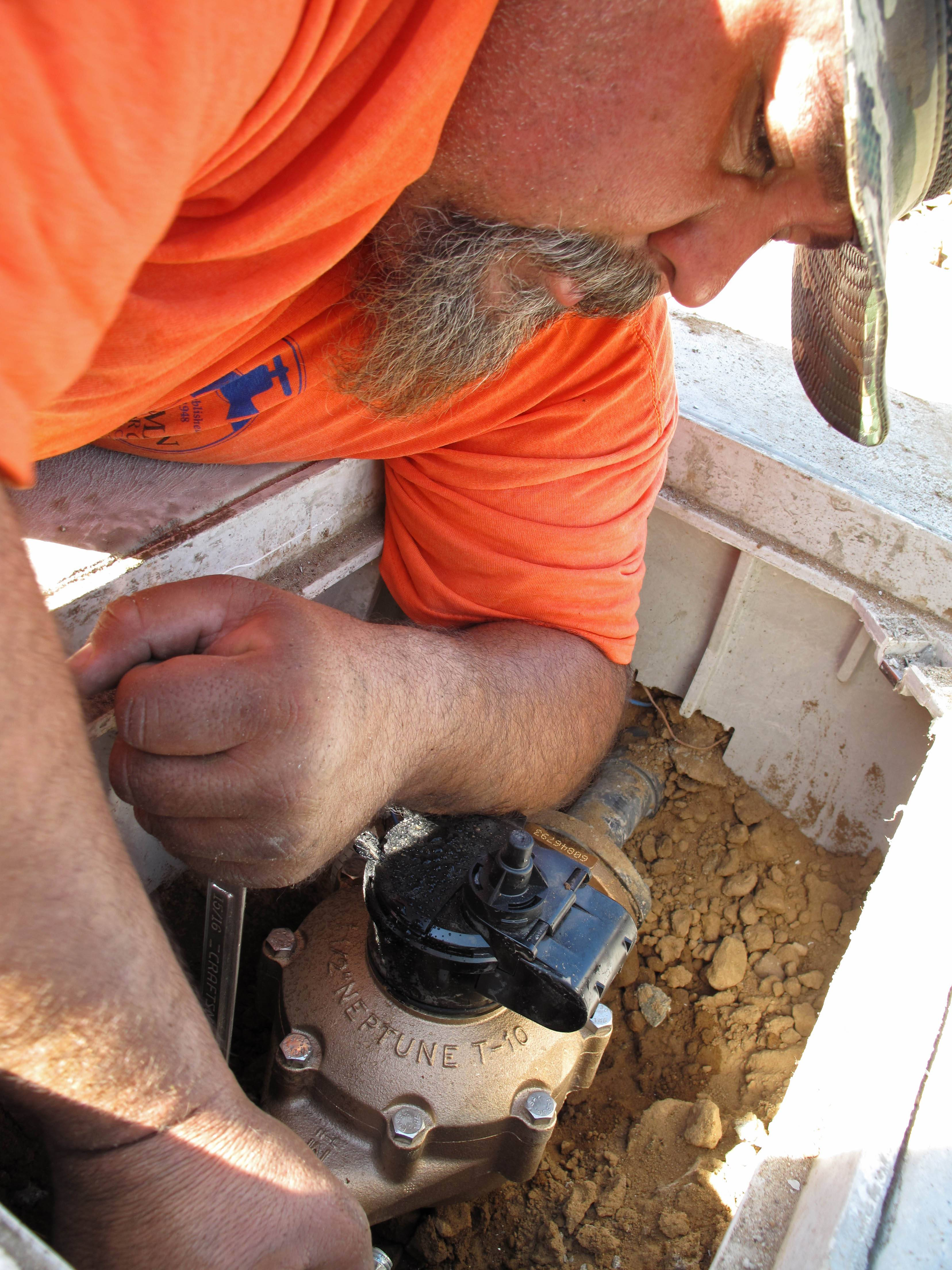 Chris Coronado, a field technician for Bakman Water Co., installs a water meter Thursday on a new home under construction in Fresno, Calif.