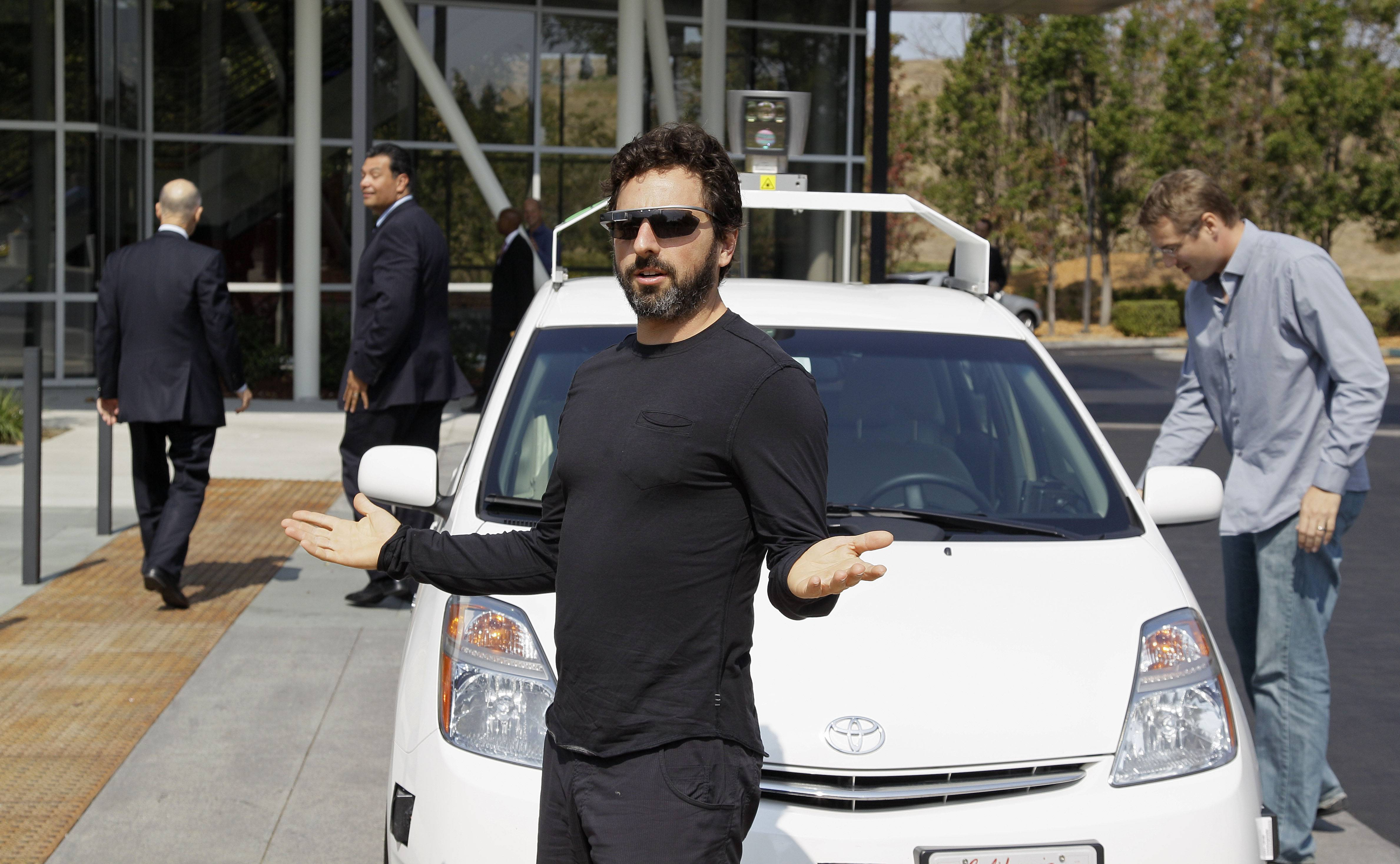 Google co-founder Sergey Brin gestures after riding in a driverless car with officials. The prospect of cars being controlled by online navigation systems is troubling to regulators and law enforcers.