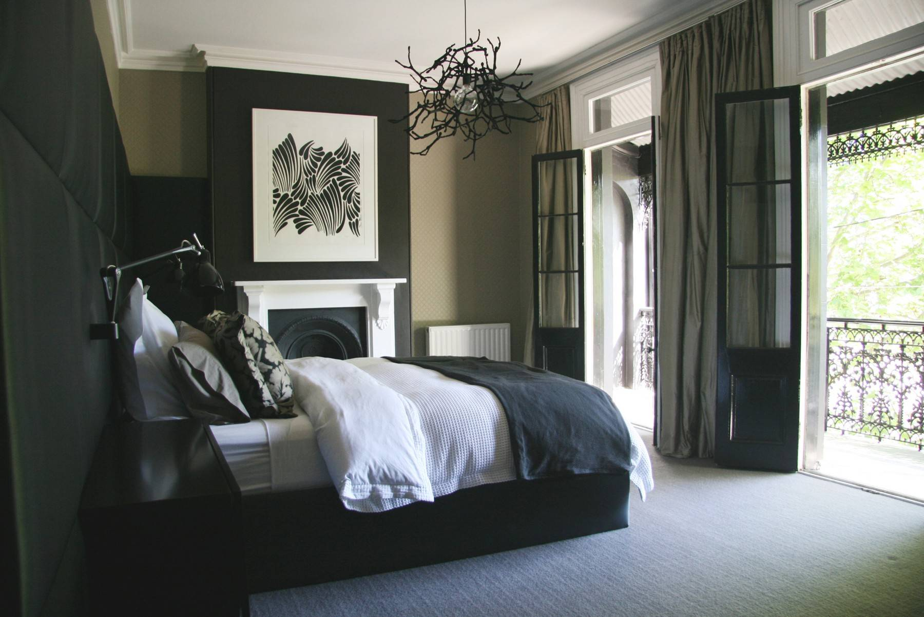 "This khaki and black bedroom is an example of ""masculine minimalism."" Though accessories are kept to a minimum, a ""work-of-art"" light fixture hangs overhead."