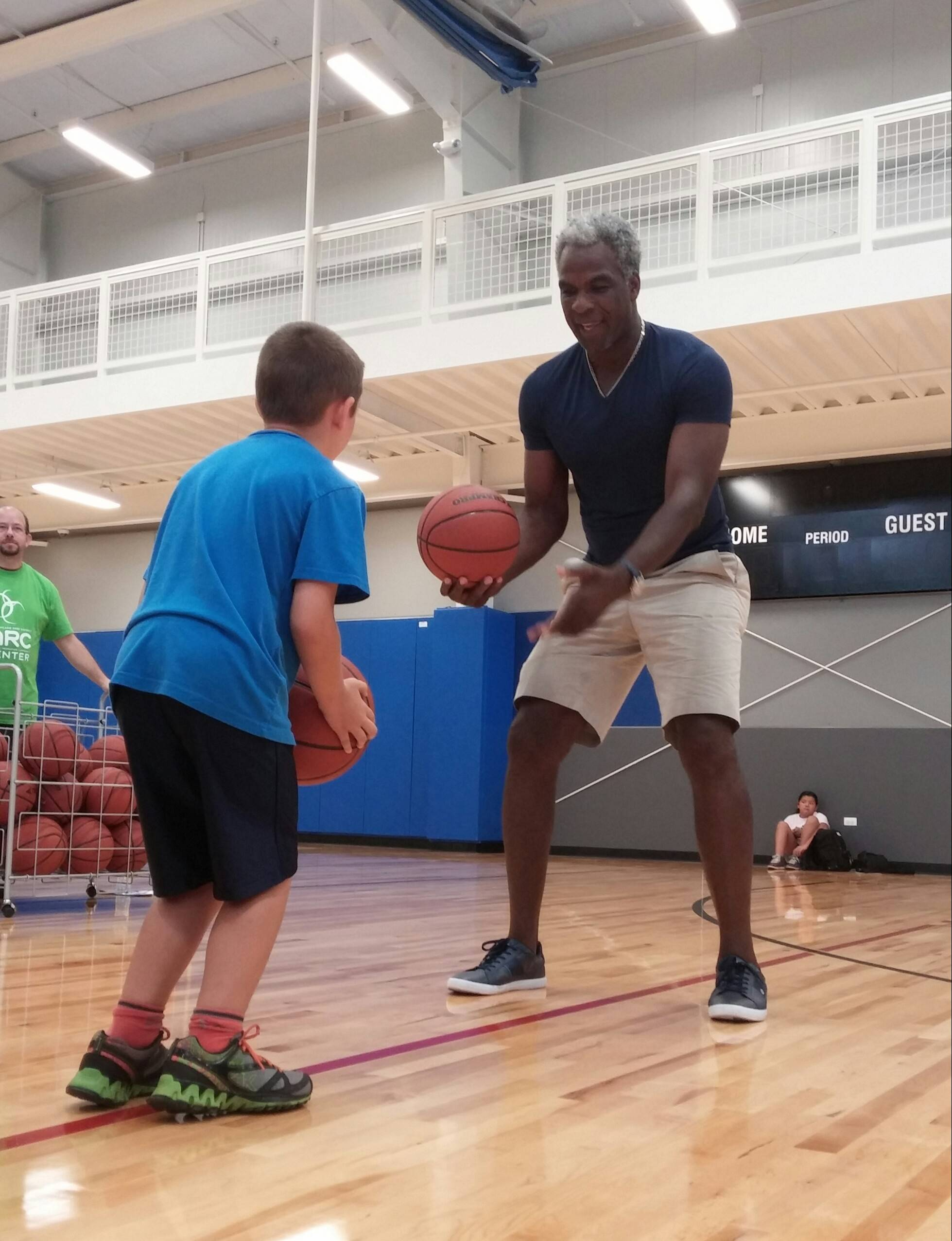 Former Chicago Bull Charles Oakley gives some dribbling tips during a clinic in the gym at West Chicago's new ARC Center grand opening Saturday. Construction on the city's first recreation center began in August 2013.