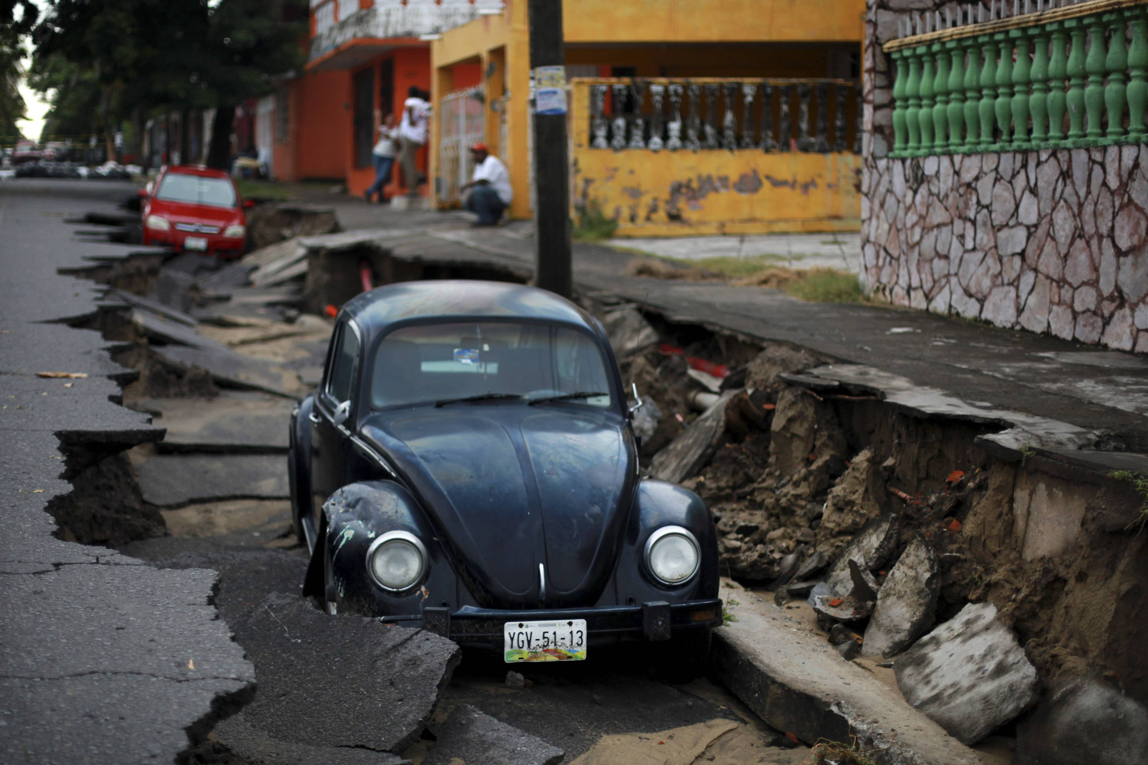 Cars sit on a street that collapsed after heavy rain Thursday in the Gulf port city of Veracruz, Mexico.