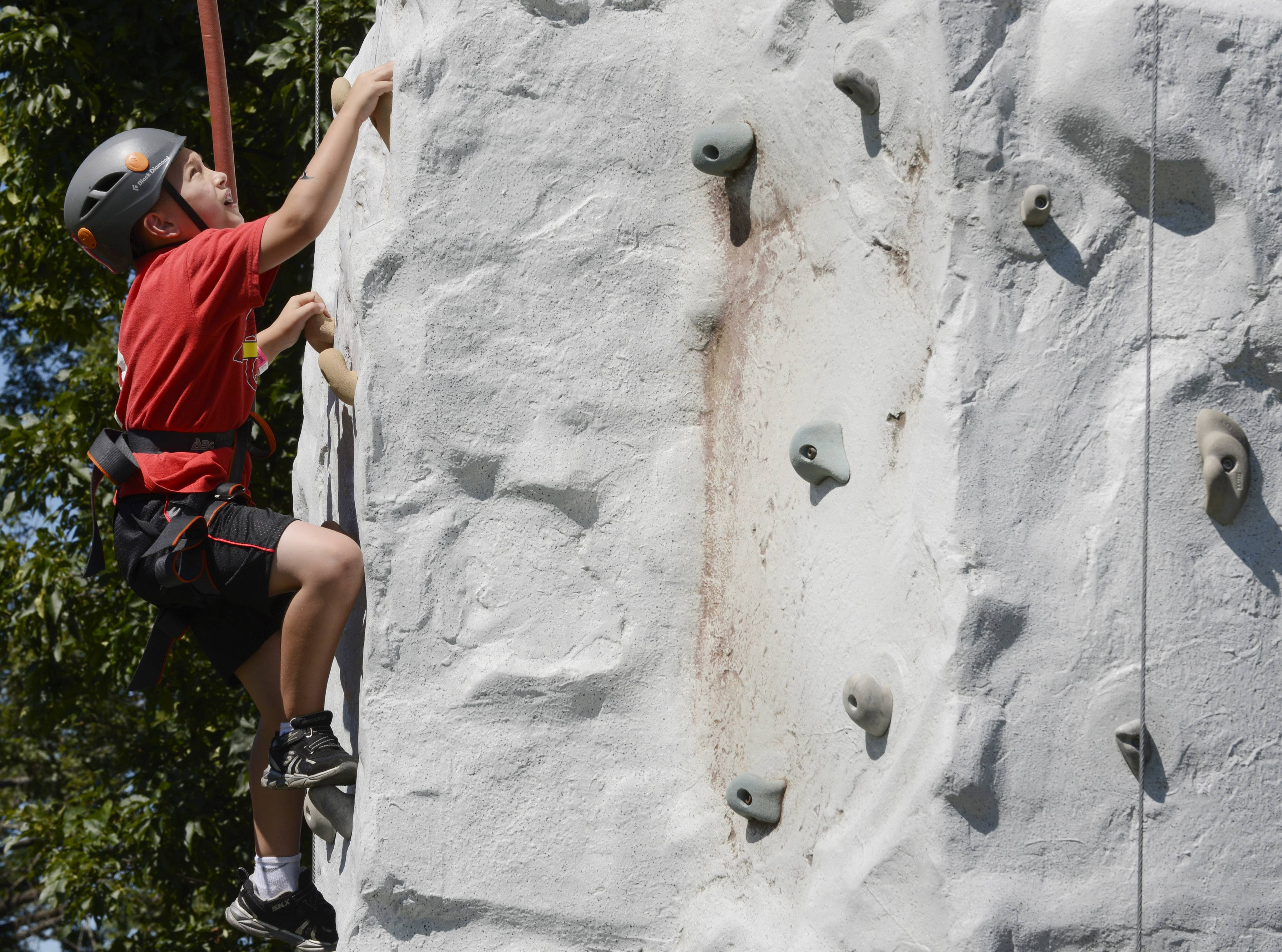 Jacob Chrzastowski, 7, of Round Lake climbs to the top of the climbing wall, hosted by the Boy Scouts, during the Round Lake Home Town Festival Saturday.