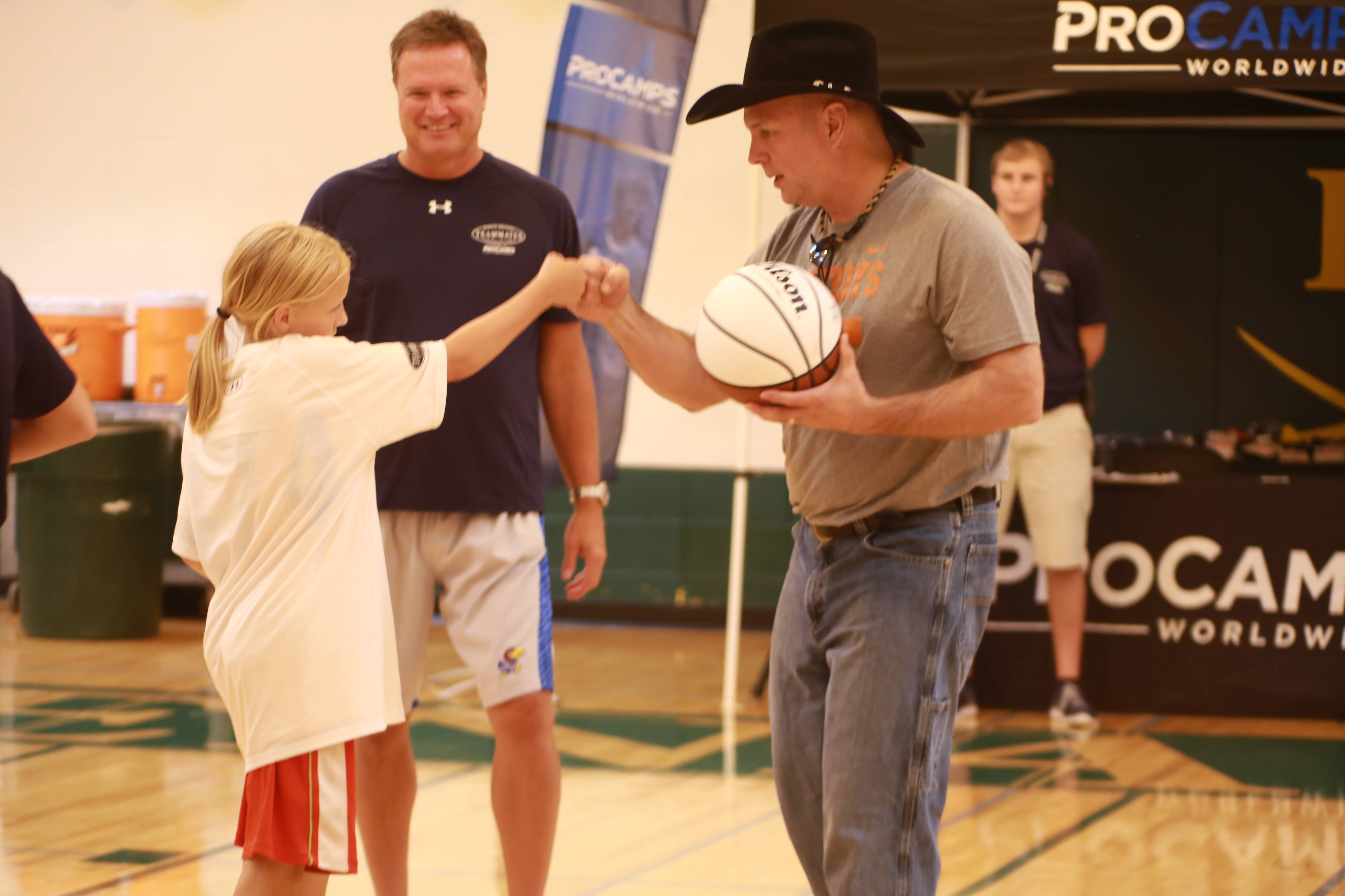 Country music superstar Garth Brooks, in his black hat, and his old college buddy, University of Kansas head basketball coach Bill Self, share a moment with a young camper Saturday at the ProCamps baskebaball camp at Elk Grove High School.
