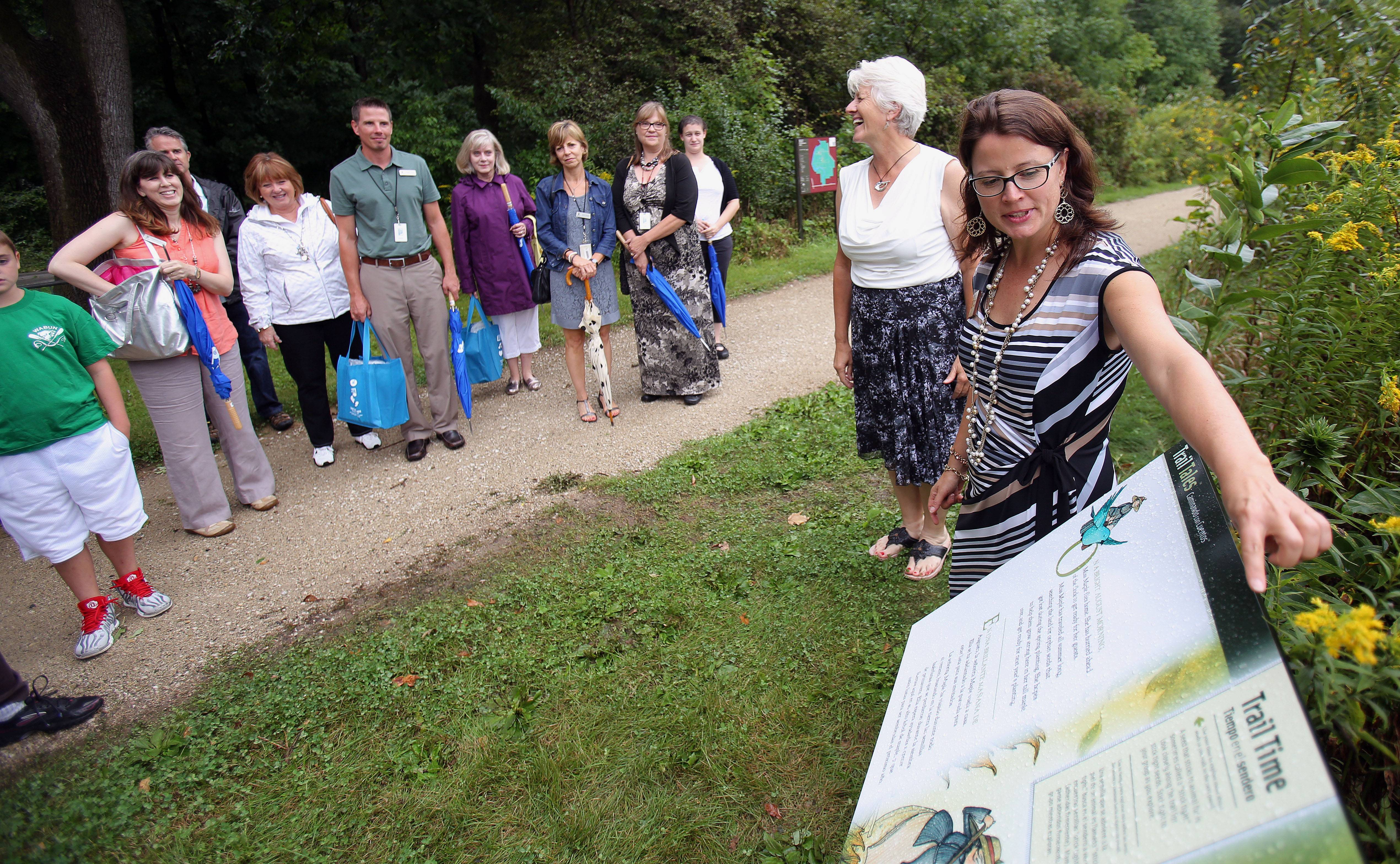 "Sophie Twichell, executive director of the Brushwood Center at Ryerson Woods, shows off a panel on a new walking and reading trail Friday at Ryerson Woods Forest Preserve near Riverwoods. The panels are taken from the children's book ""Miss Maple's Seeds."""