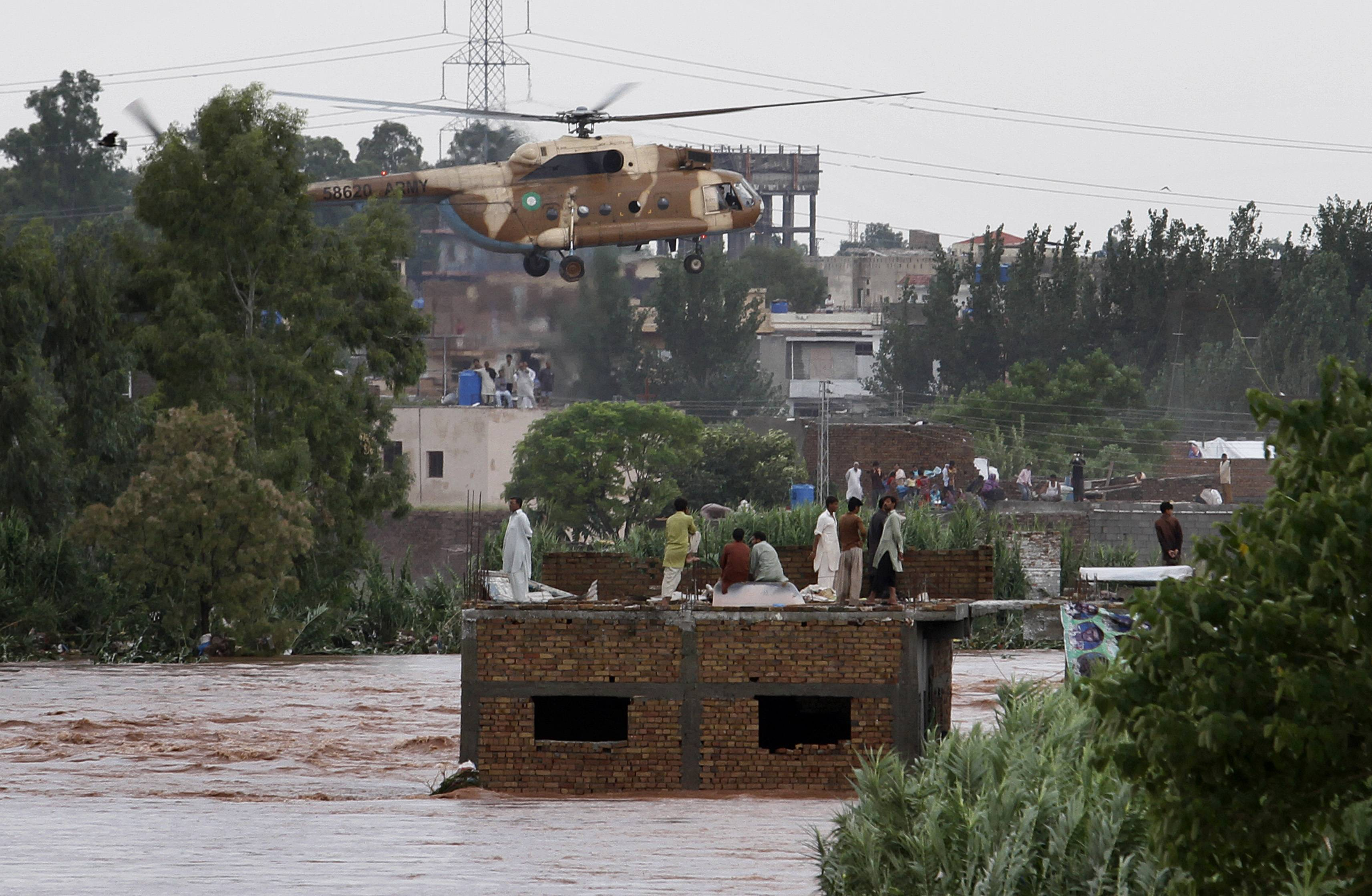 An Pakistani army helicopter hovers to rescue trapped people Friday from a flooded area on the outskirts of Islamabad, Pakistan. Heavy monsoon rains killed dozens of people across Pakistan as flash flood inundated villages, prompting authorities to send troops to evacuate residents and assist in the emergency, officials said.