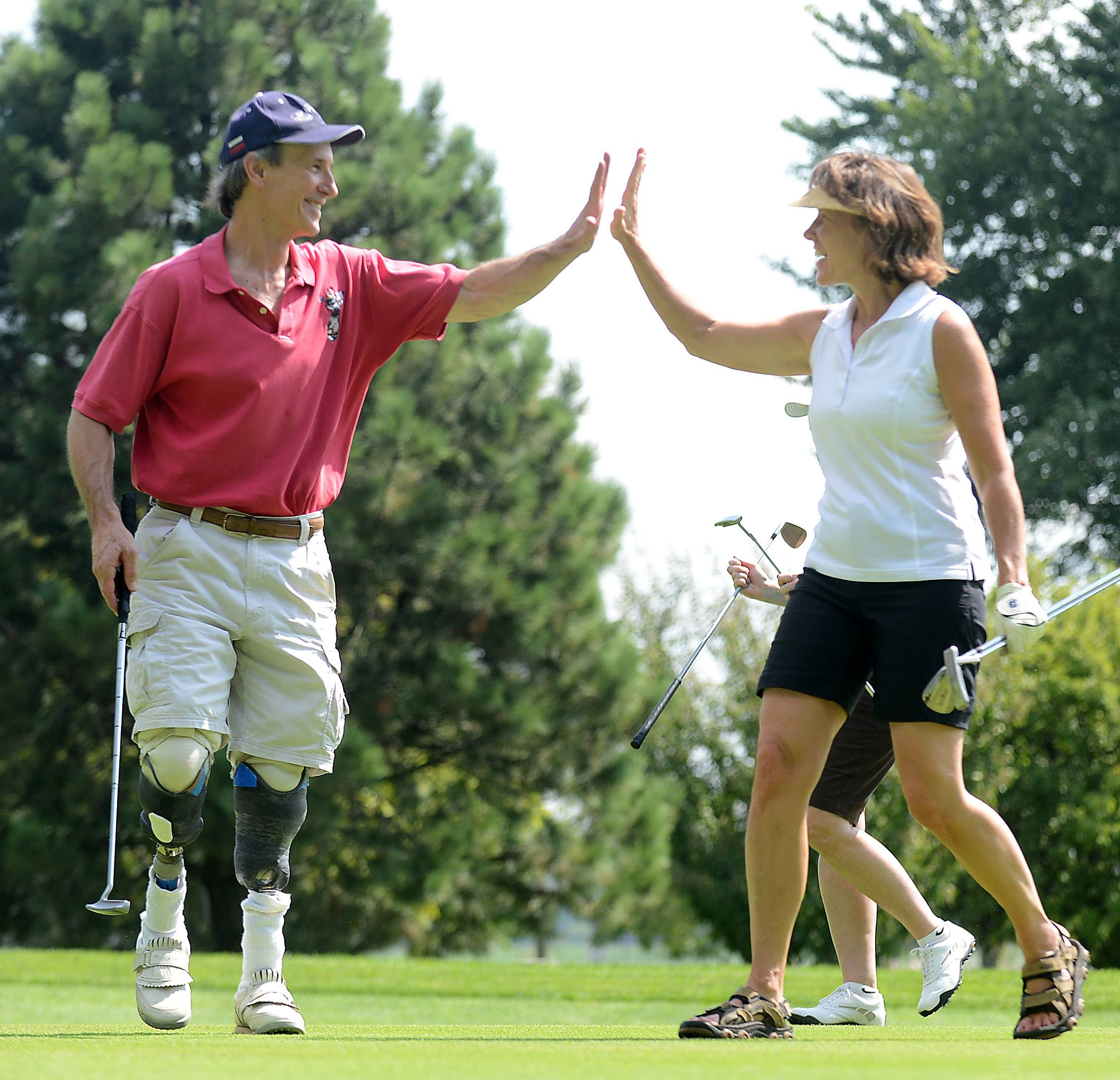 Jeff Linton of Chicago gets a high-five from Robin Carlson of Berwyn after he sank a putt during a scramble fundraising round Friday at the 14th annual Midwestern Amputee Golf Association tournament at Pheasant Run in St. Charles. Linton lost his legs in an accident in college and later picked up golf.