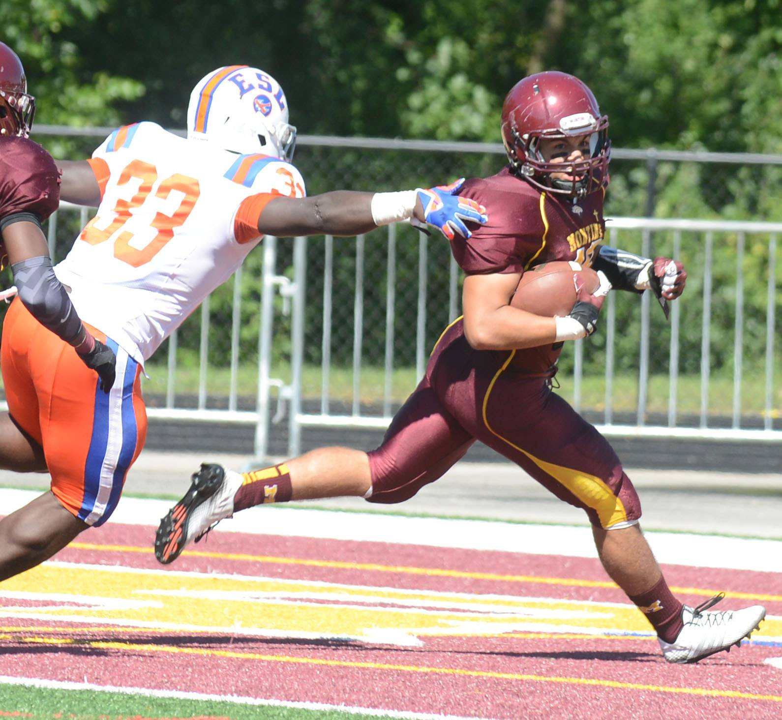 Samuel Asta of Montini scores while Jerod Robinson of East St. Louis chases during Saturday's game in Lombard.