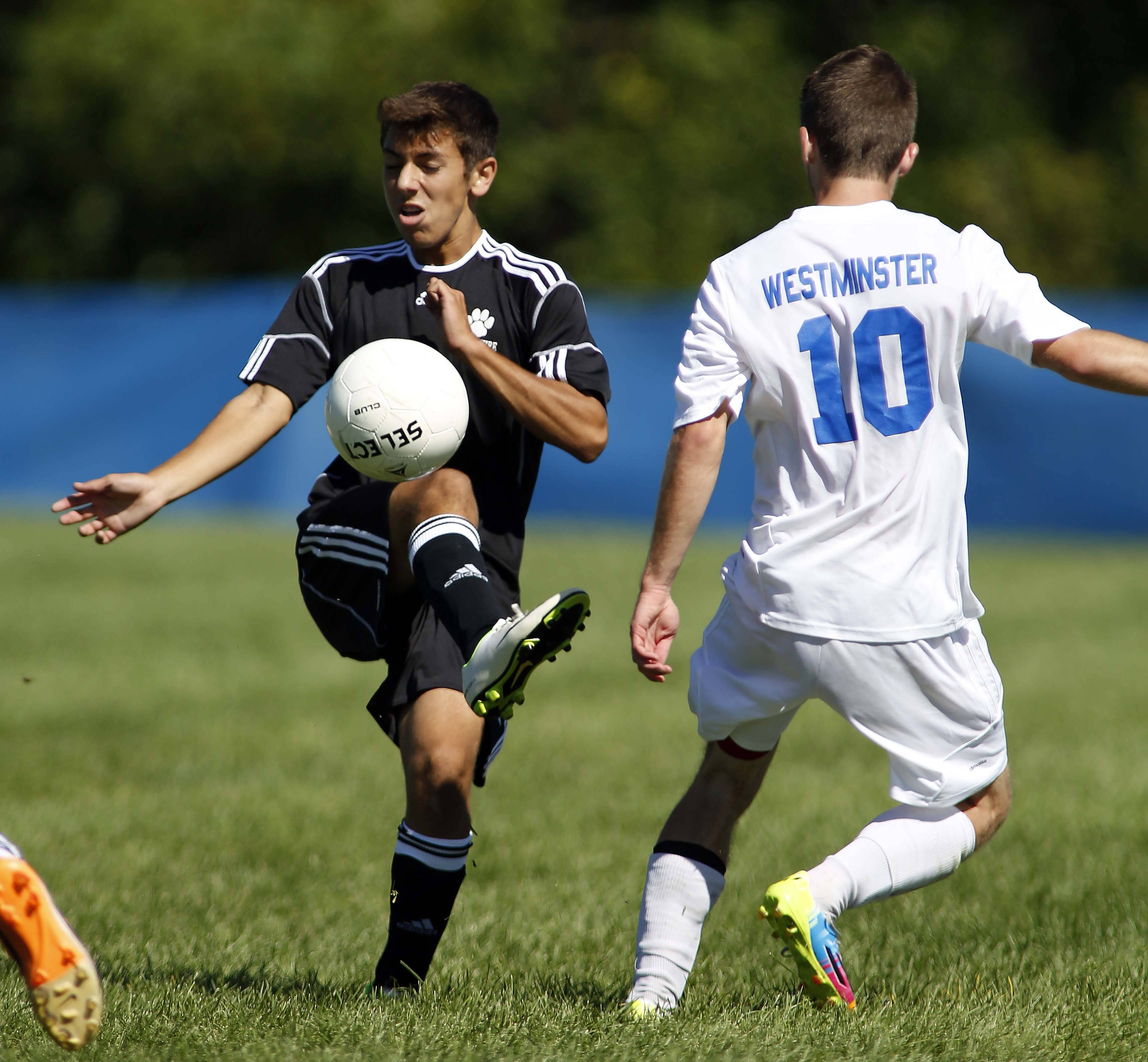 Hampshire's Charlie Piazza (2) battles Westminster Christian's Noah Gannon for control during soccer action at Westminster Christian in Elgin Saturday.