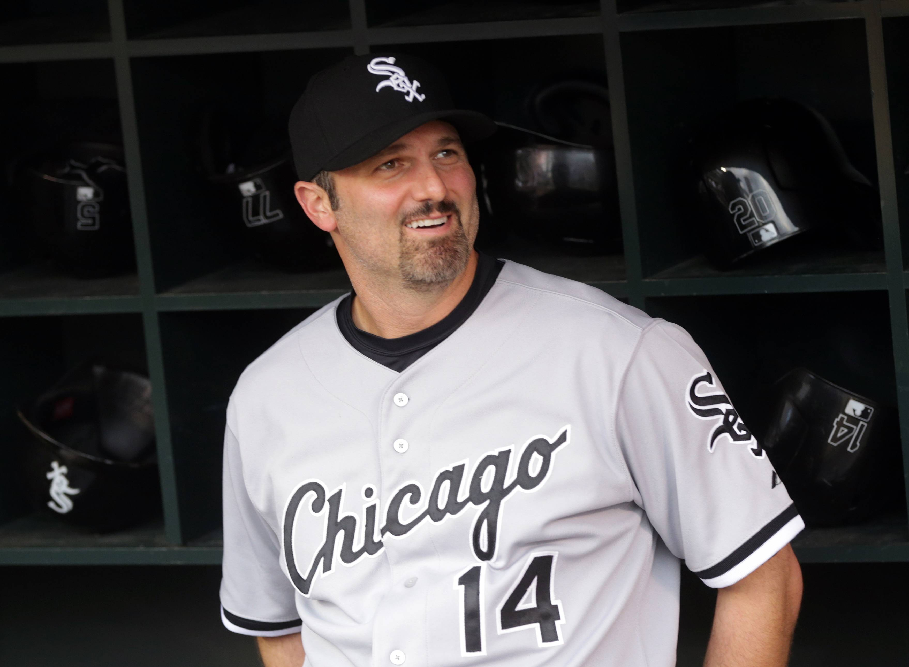 Chicago White Sox' Paul Konerko watches video highlights before he was presented a large bottle of wine by Minnesota Twins' Joe Mauer and Glen Perkins before Wednesday's game.