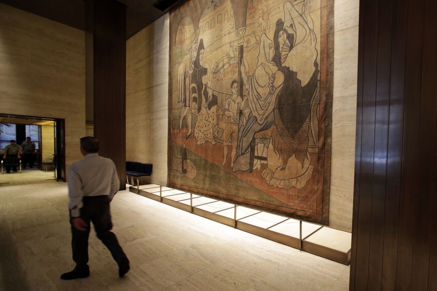 "A man walks past Picasso's ""Le Tricorne,"" a 19-foot by 20-foot stage curtain, hangs in the lobby of the Seagram building, in a passageway connecting the two dining rooms of New York's Four Seasons restaurant."