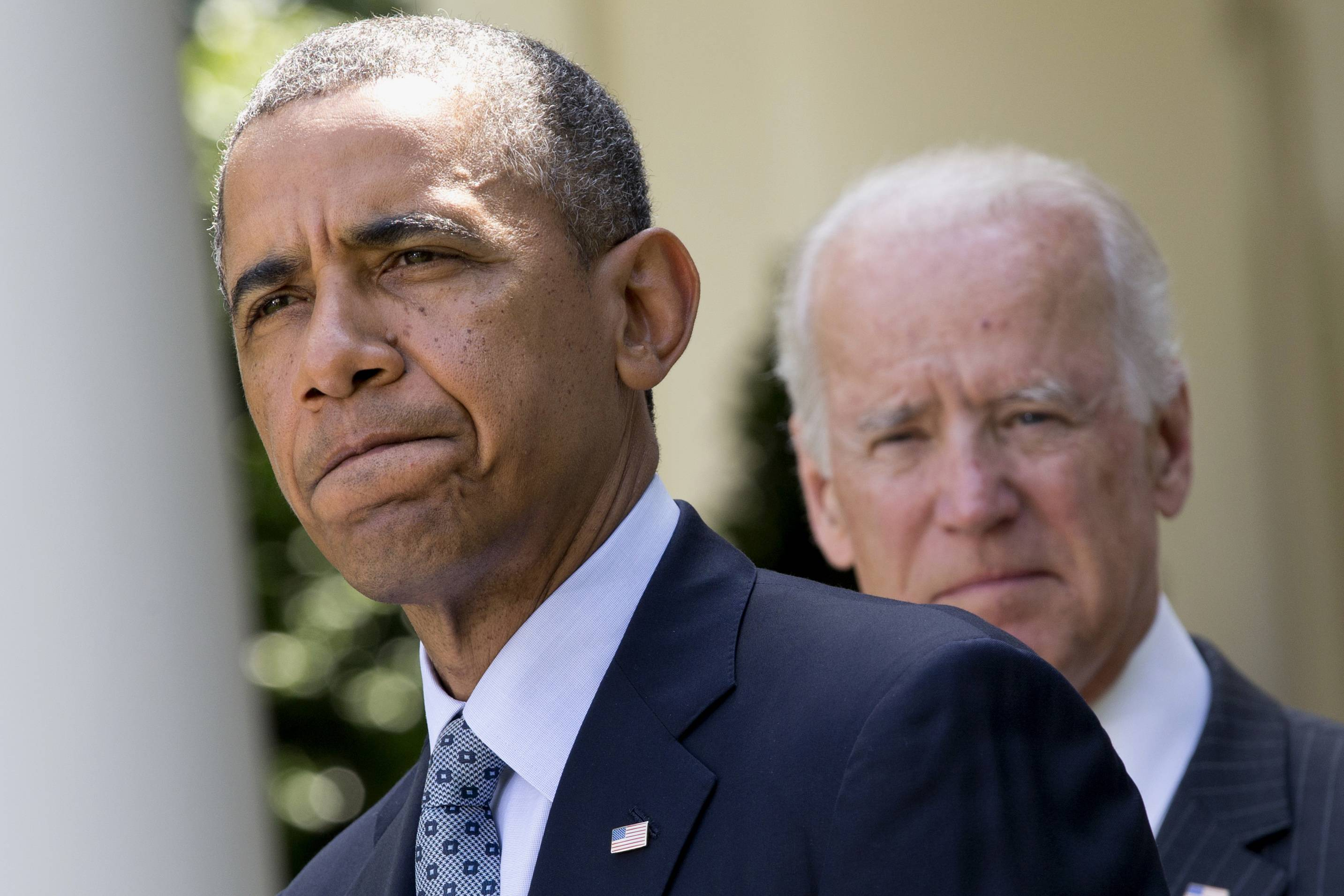 President Barack Obama, accompanied by Vice President Joe Biden, pauses while making an announcement about immigration reform in the Rose Garden of the White House in Washington.