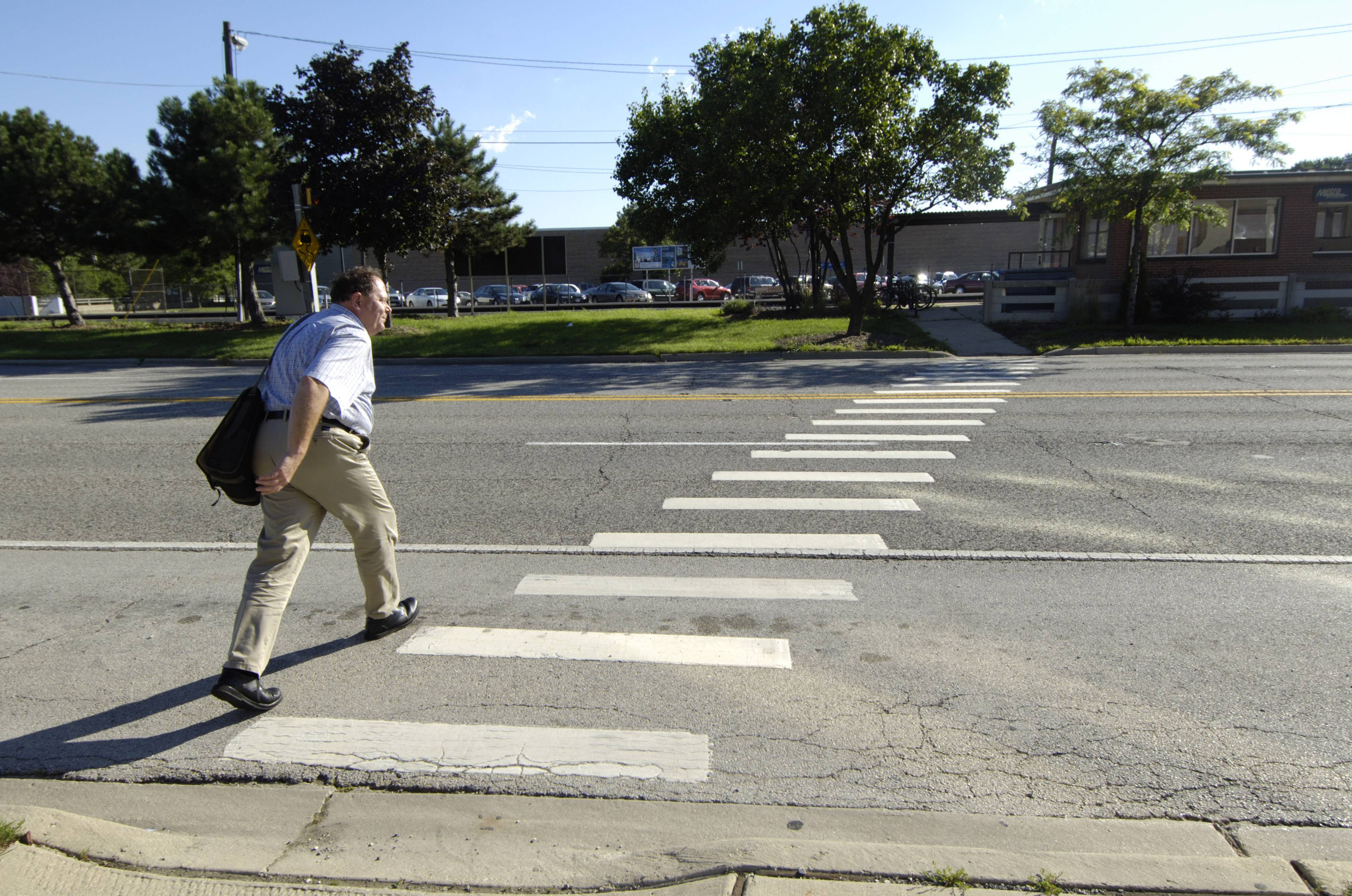 A pedestrian crosses Northwest Highway in front of the Cumberland Metra station in Des Plaines.