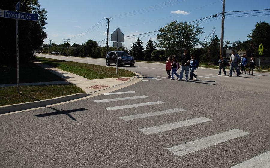 A car stops for students in the crosswalk at Miller Road and Providence Drive in Carpentersville.