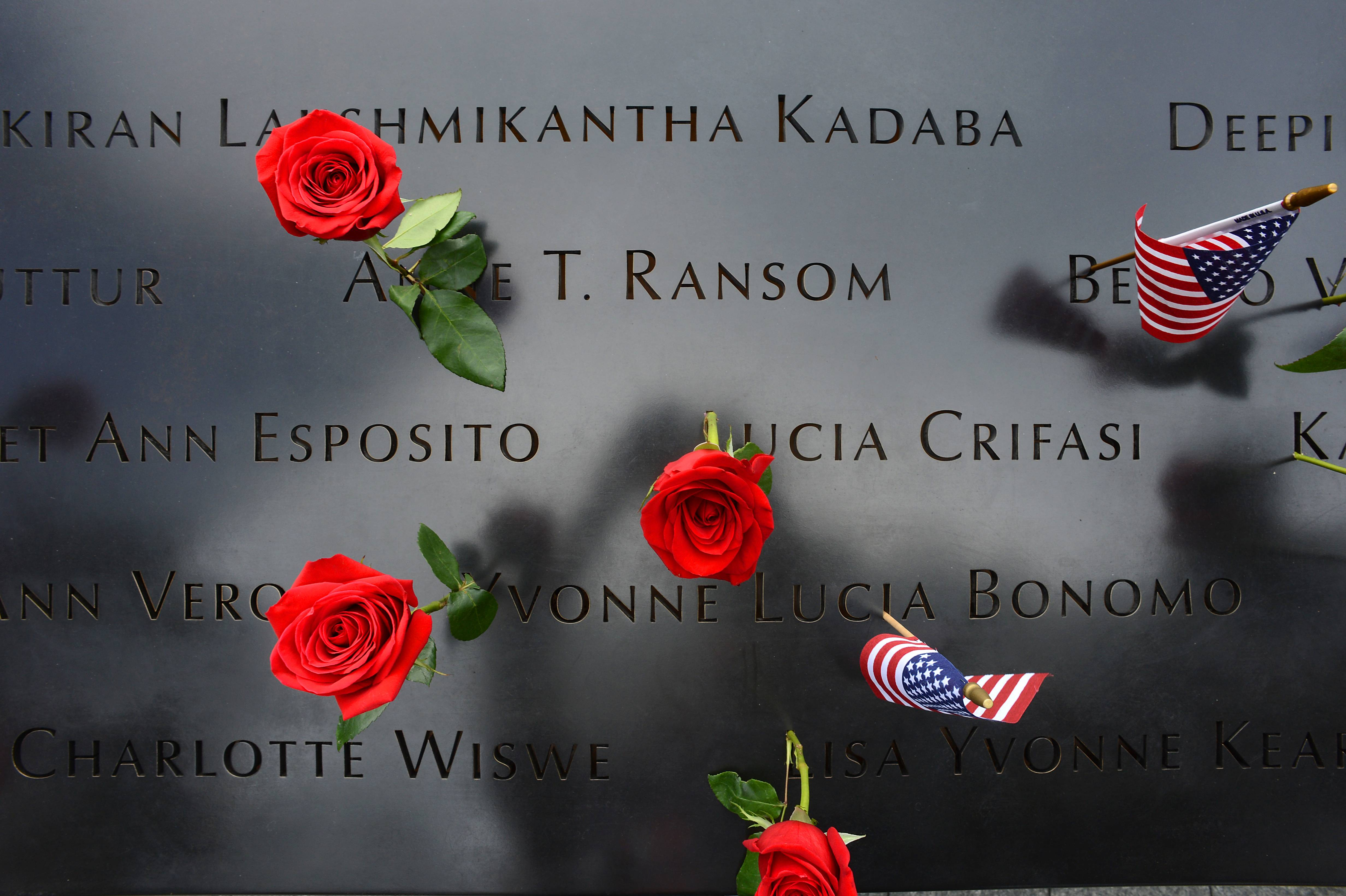 Roses and flags left by loved ones are placed on the names inscribed at the North Pool during memorial observances on the 13th anniversary of the Sept. 11 terror attacks on the World Trade Center in New York, Thursday, Sept. 11, 2014. Family and friends of those who died read the names of the nearly 3,000 people killed in New York, at the Pentagon and near Shanksville, Pennsylvania.