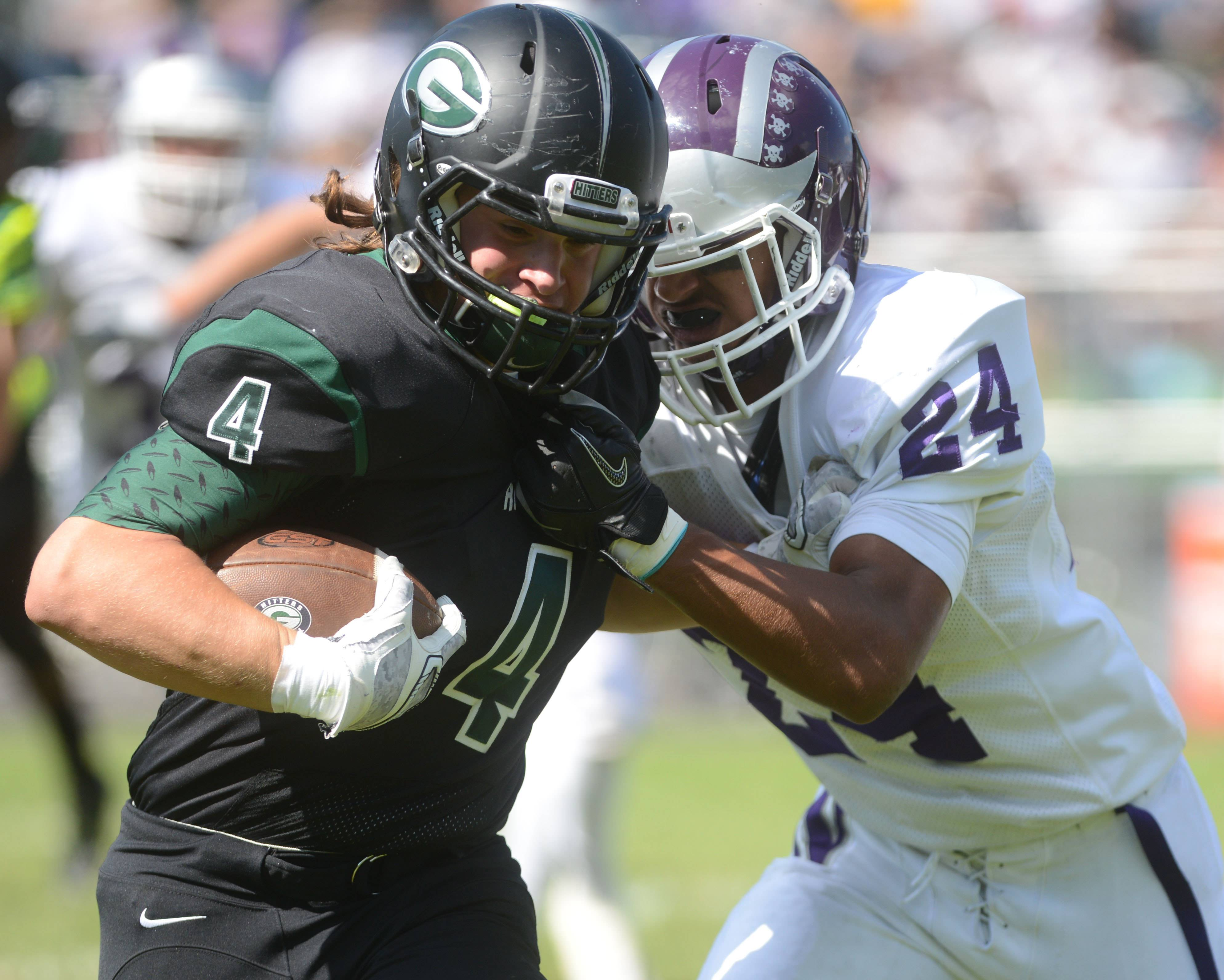 Sam Brodner of Glenbard West moves the ball around Kendrick Schultz of Downers Grove North during the Downers Grove North at Glenbard West football game Saturday.