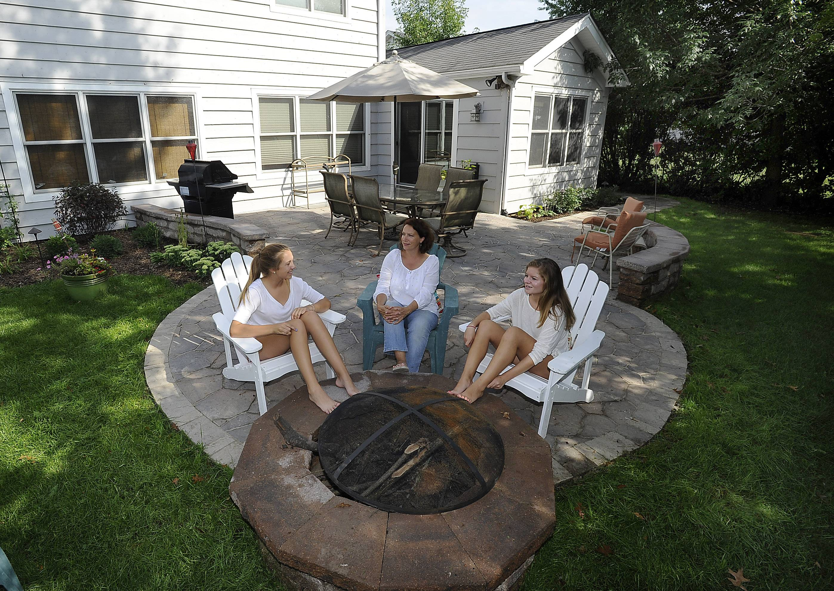 Jenny Kendall of Palatine, center, won a patio makeover package that included new plants, lights, stone pavers and this fire pit as daughter Caroline Kendall, left, and her friend Greta Smolak enjoy this new spot.