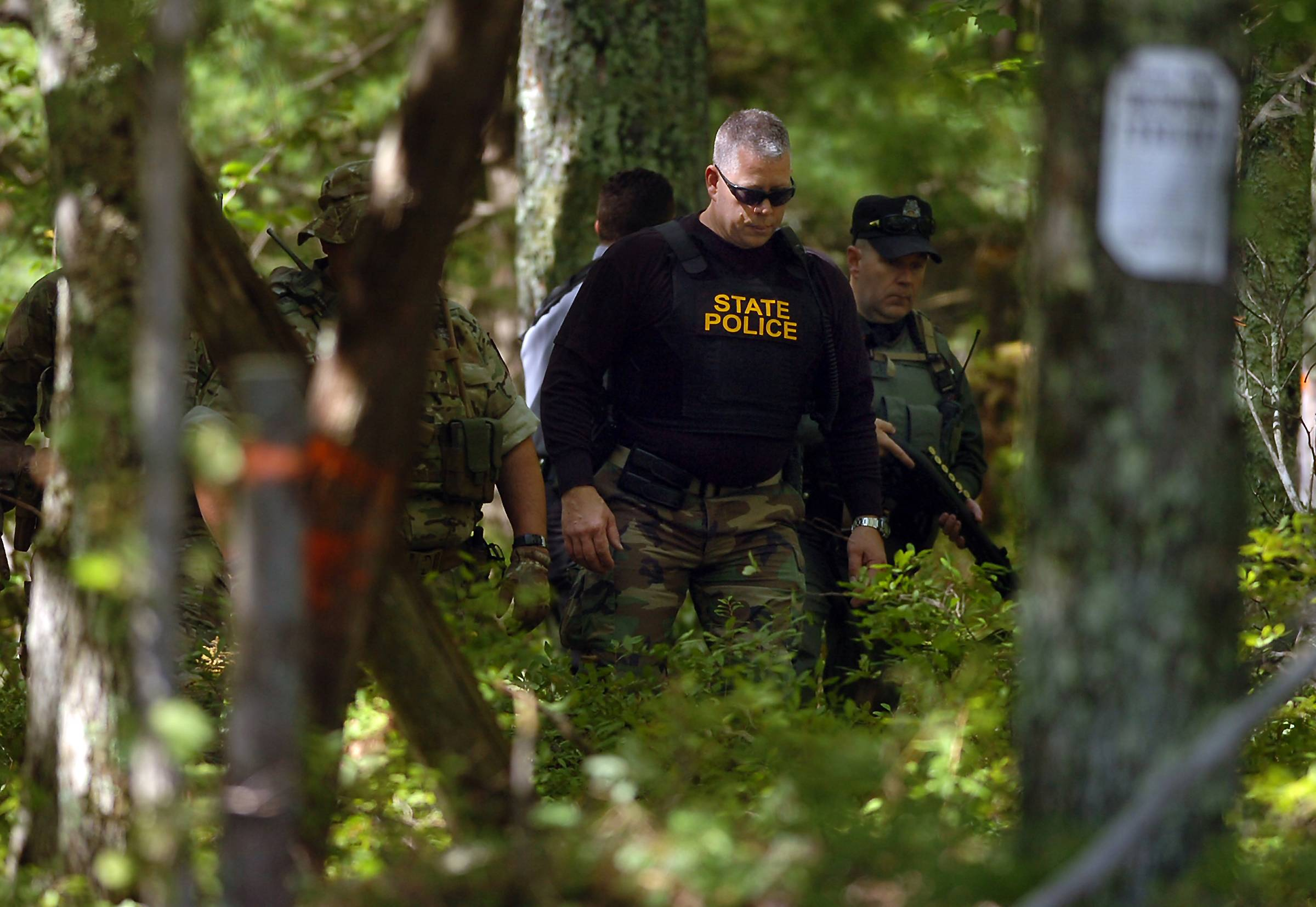 A Pennsylvania state trooper and others investigate a wooded area across from the police barracks Sunday in Blooming Grove Township, Pa., near where, on Friday night, a state trooper was killed and another wounded after a shooting ambush at the barracks. No arrests have been made.