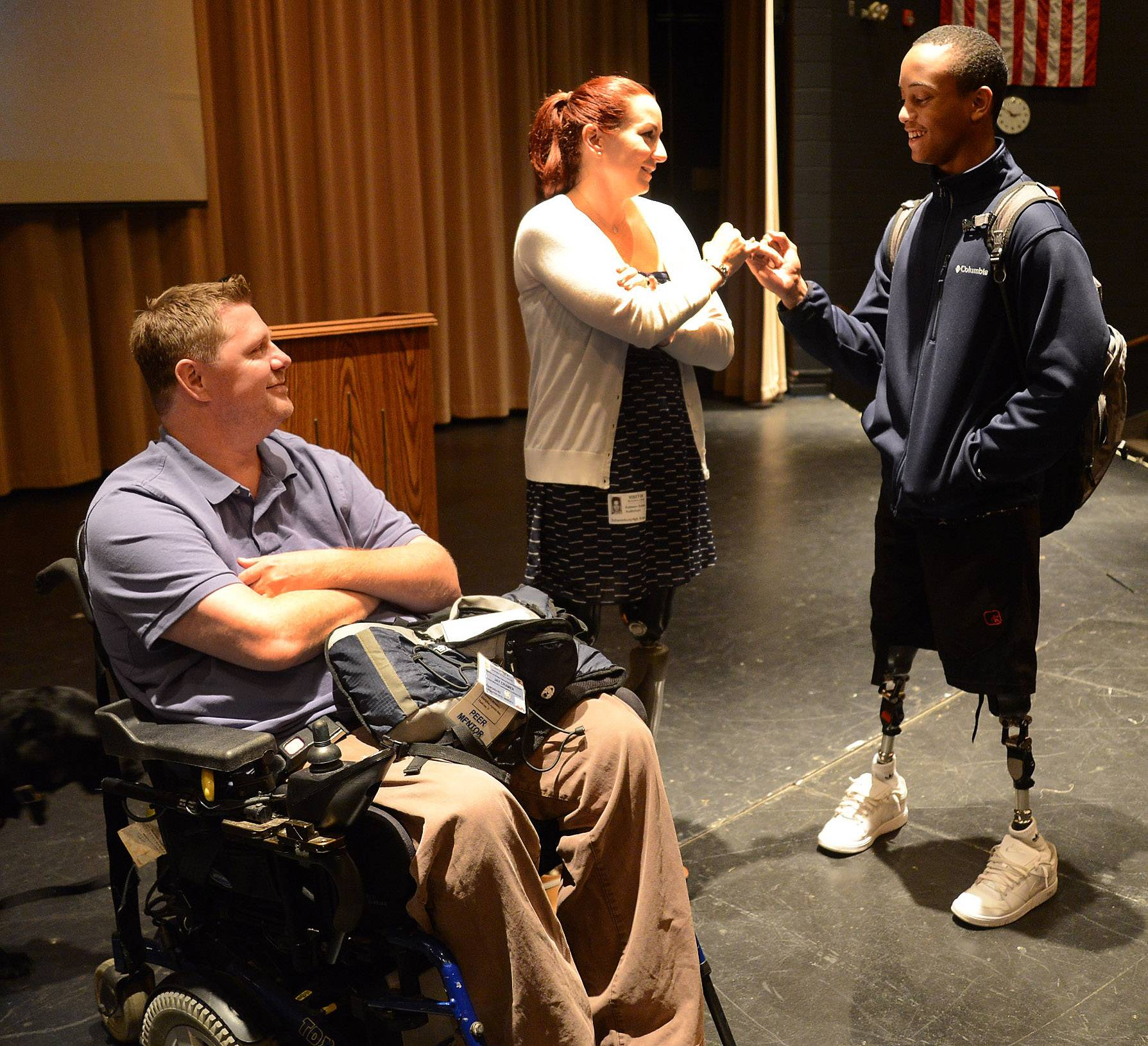 Jay Cramer and his wife, Katy Sullivan, meet with Schaumburg High student Sabik Cohran, born without legs.