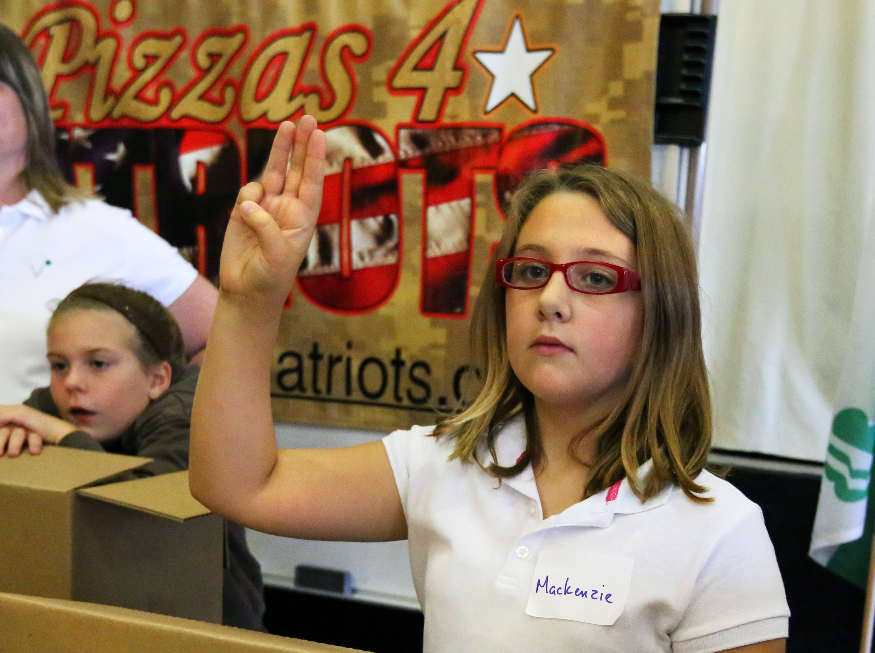 Vowing to do her part as a Girl Scout, Mackenzie Nylander, 11, of Elk Grove Village, makes the Scout sign. Leader Frances Lehning organized girls at Lutheran Church of the Holy Spirit in Elk Grove Village, where they packed 13,000 boxes of Girl Scout cookies to be shipped to veterans in all 50 states.