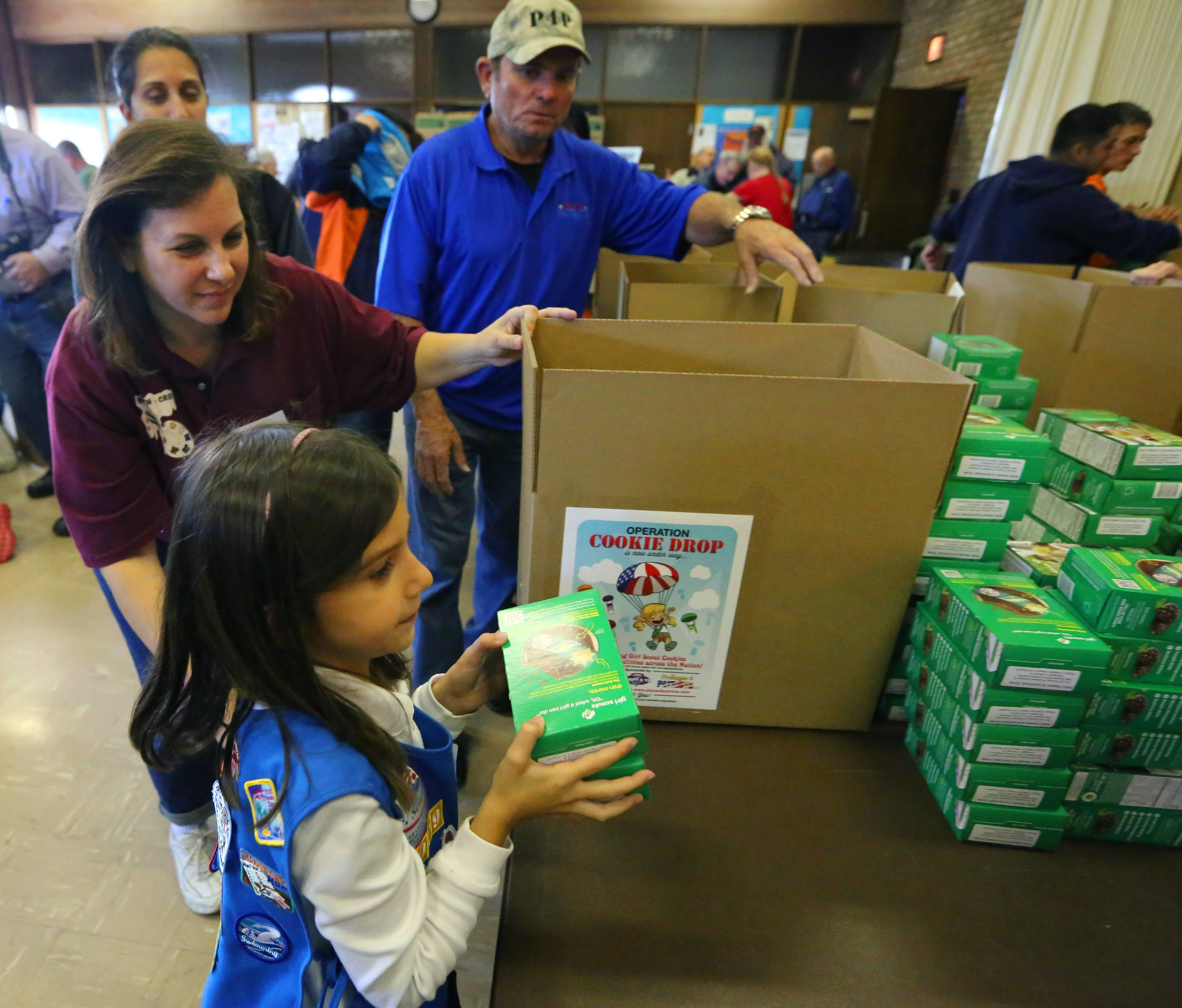 Girl Scout leader Frances Lehning and Pizza 4 Patriots founder Mark Evans watch as Immacolata Papucci, 7, of Elk Grove Village, packs one of 13,000 boxes of cookies on their way to veterans as part of Operation Cookie Drop.