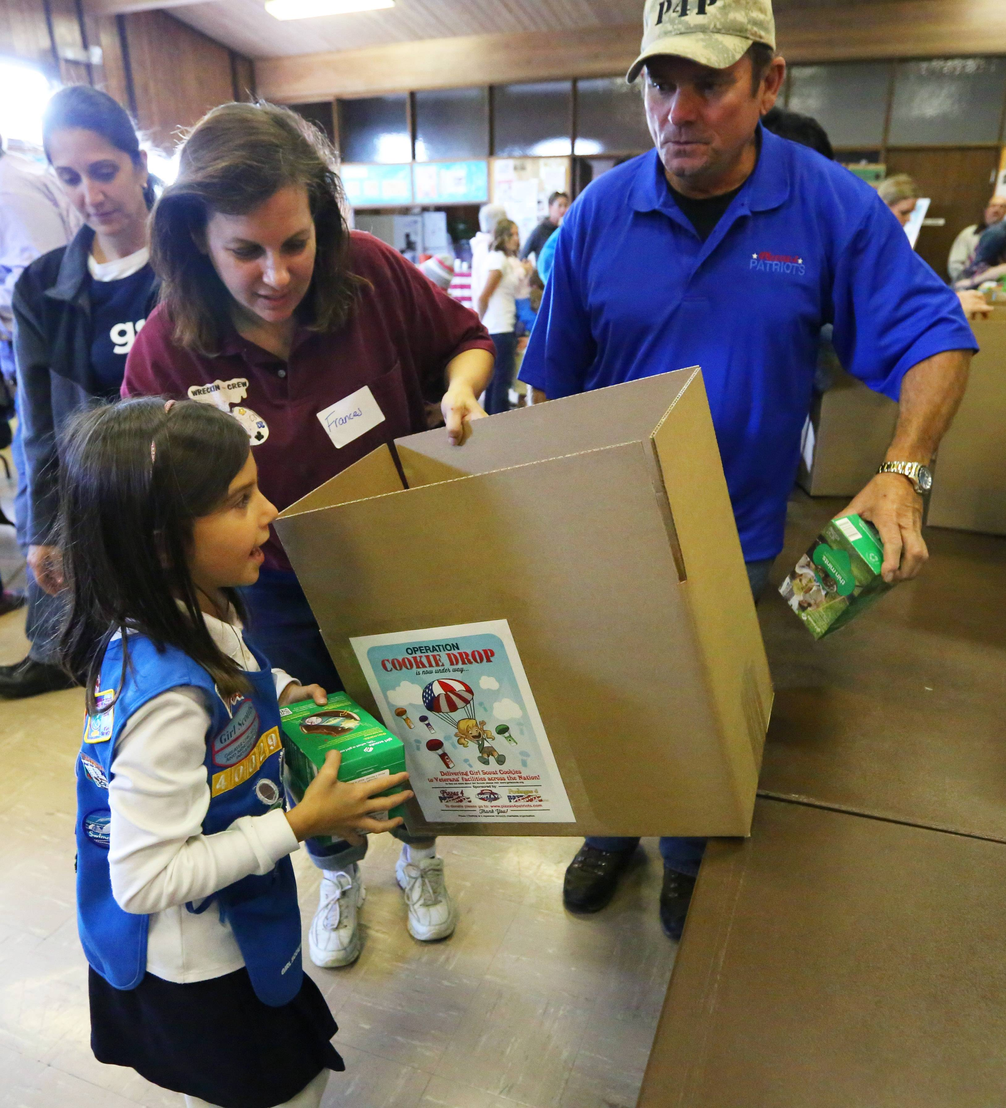 Learning how to pack 40 boxes of cookies into one shipping box, Immacolata Papucci, 7, of Elk Grove Village, follows the advice of Operation Cookie Drop leader Frances Lehning and Pizza 4 Patriots founder Mark Evans.