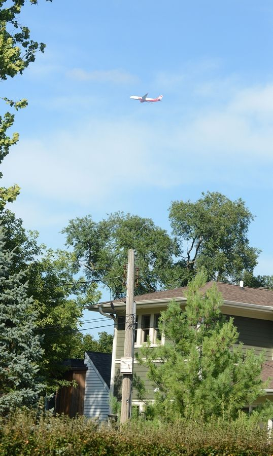 A plane flies low over Itasca's Washington Street. Jet noise complaints in Itasca went from 41 in July 2013 to 1,121 this July.