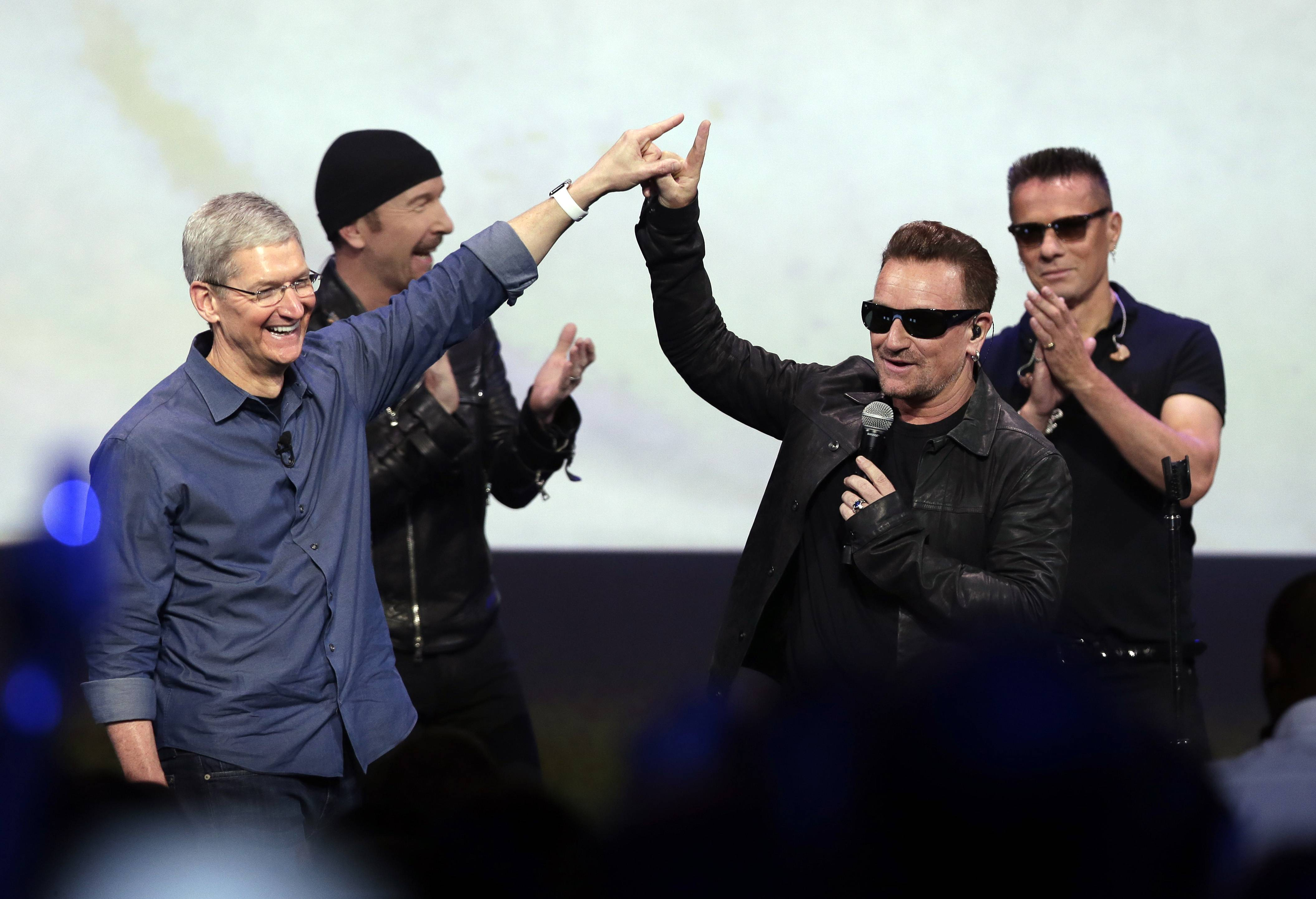 Apple CEO Tim Cook, left, greets Bono from the band U2 after they performed at the end of the Apple iPhone 6 announcement event on Tuesday, Sept. 9, in Cupertino, Calif.