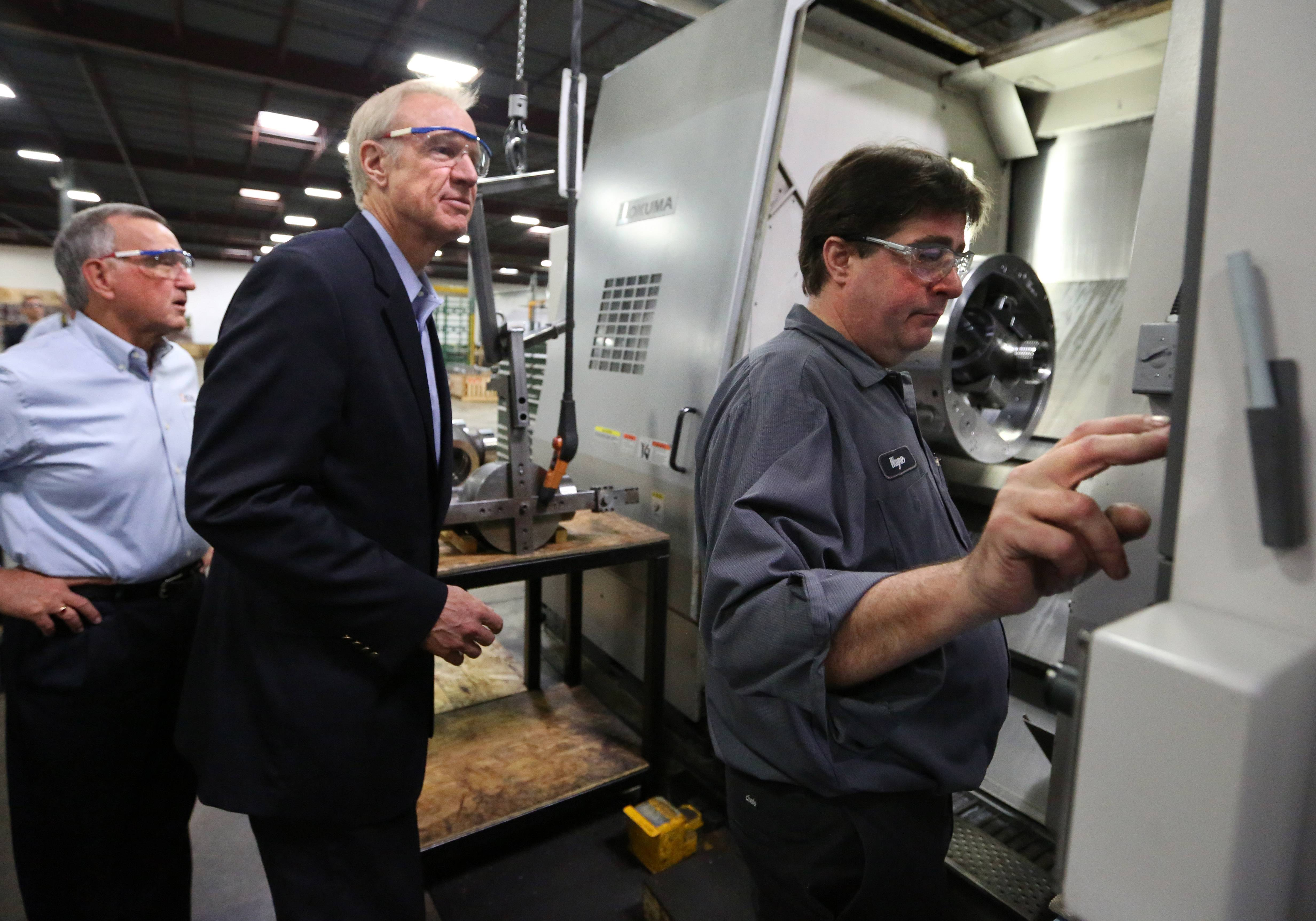 Republican gubernatorial candidate Bruce Rauner, center, watches machinist Wayne Follman, right, adjust the controls on his machine. On Tuesday, Rauner was touring ACME Industries with Warren Young, ACME Industries chairman, left.