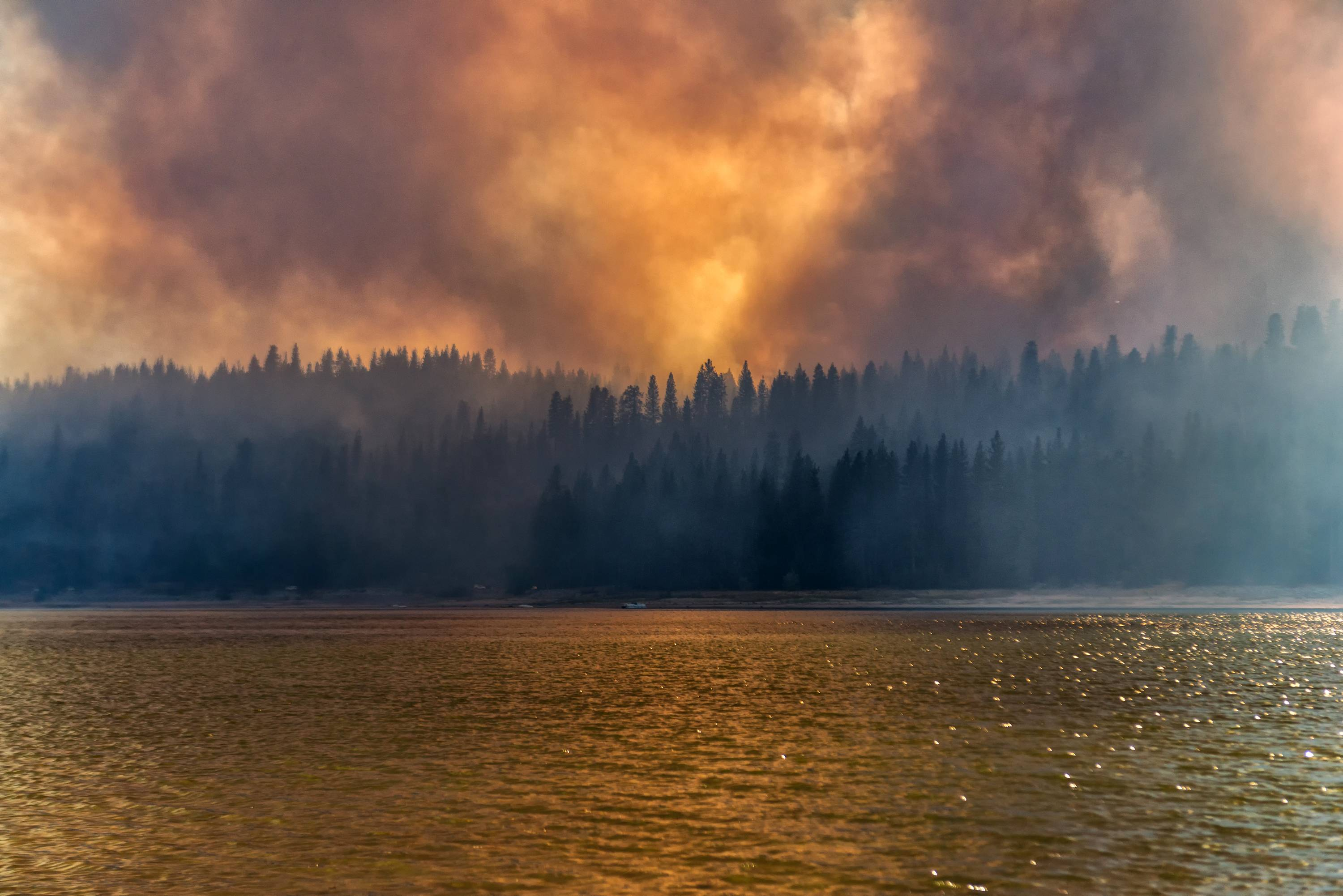 In this Sunday, Sept. 14, 2014 photo provided by YosemiteLandscapes.com, large plumes of smoke from a wildfire rise over Bass Lake, Calif. Crews attempted to get better access to two raging wildfires in California Monday that have forced hundreds to evacuate their homes. (AP Photo/YosemiteLandscapes.com, Darvin Atkeson)