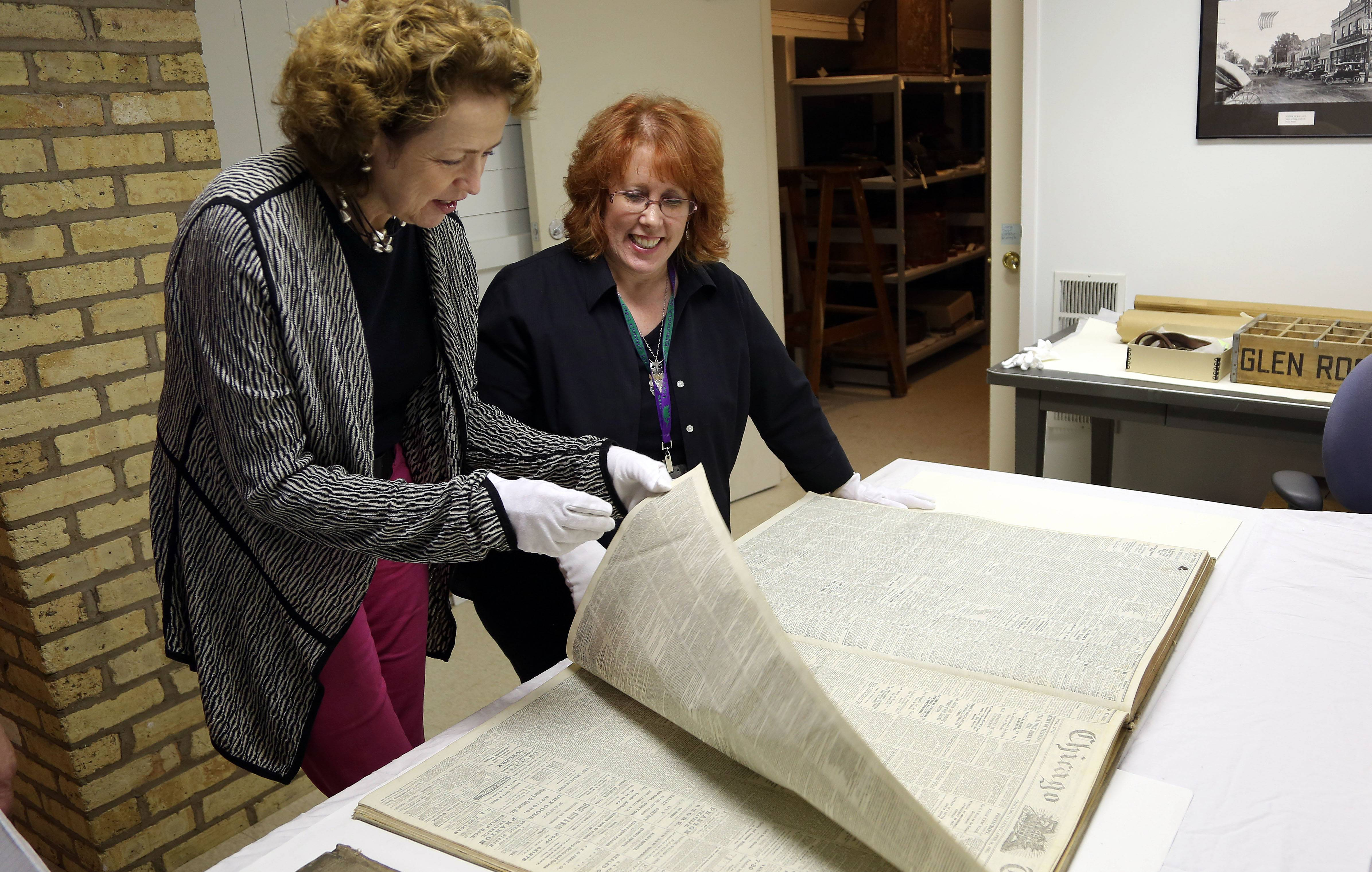 Lake County Discovery Museum Cultural Resources Director Katherine Hamilton-Smith, left, and Collections Coordinator Diana Dretske peruse the museum's collection of Civil War-era Chicago Tribune newspapers. The collection has been sold to the Robert R. McCormick Museum at Cantigny Park in Wheaton.