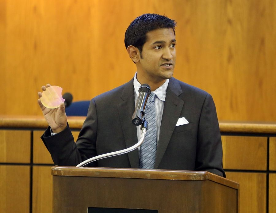 Adam Khan, founder and CEO of AKHAN Semiconductor, holds up a sample of a diamond semiconductor that would be produced at their new location in Gurnee as he speaks to community leaders at Gurnee Village Hall Tuesday night.