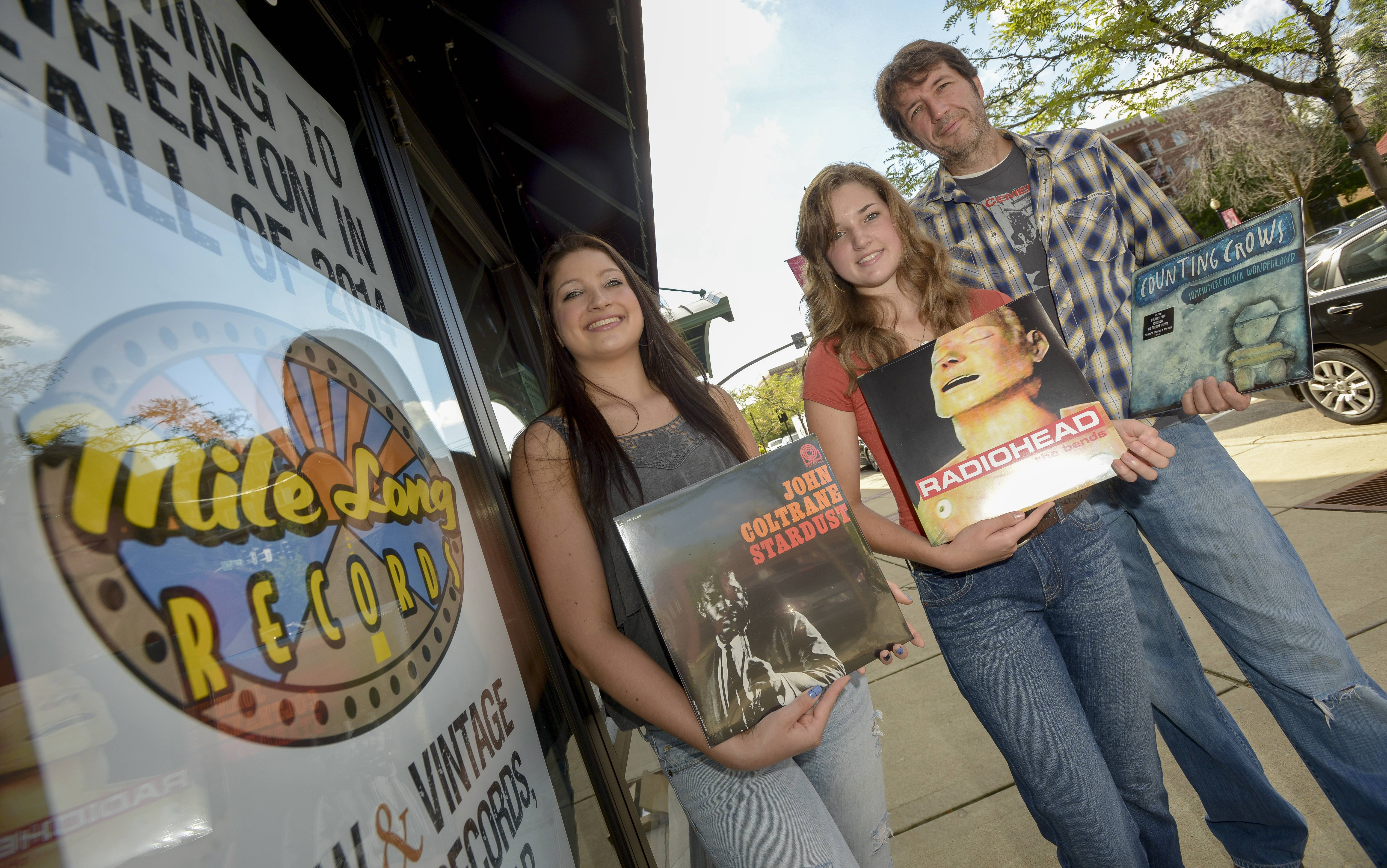 Abby and Allie Paeth hold vinyl albums their father, Michael Paeth, will carry in his Mile Long Records store, expected to open about Oct. 15 in downtown Wheaton.