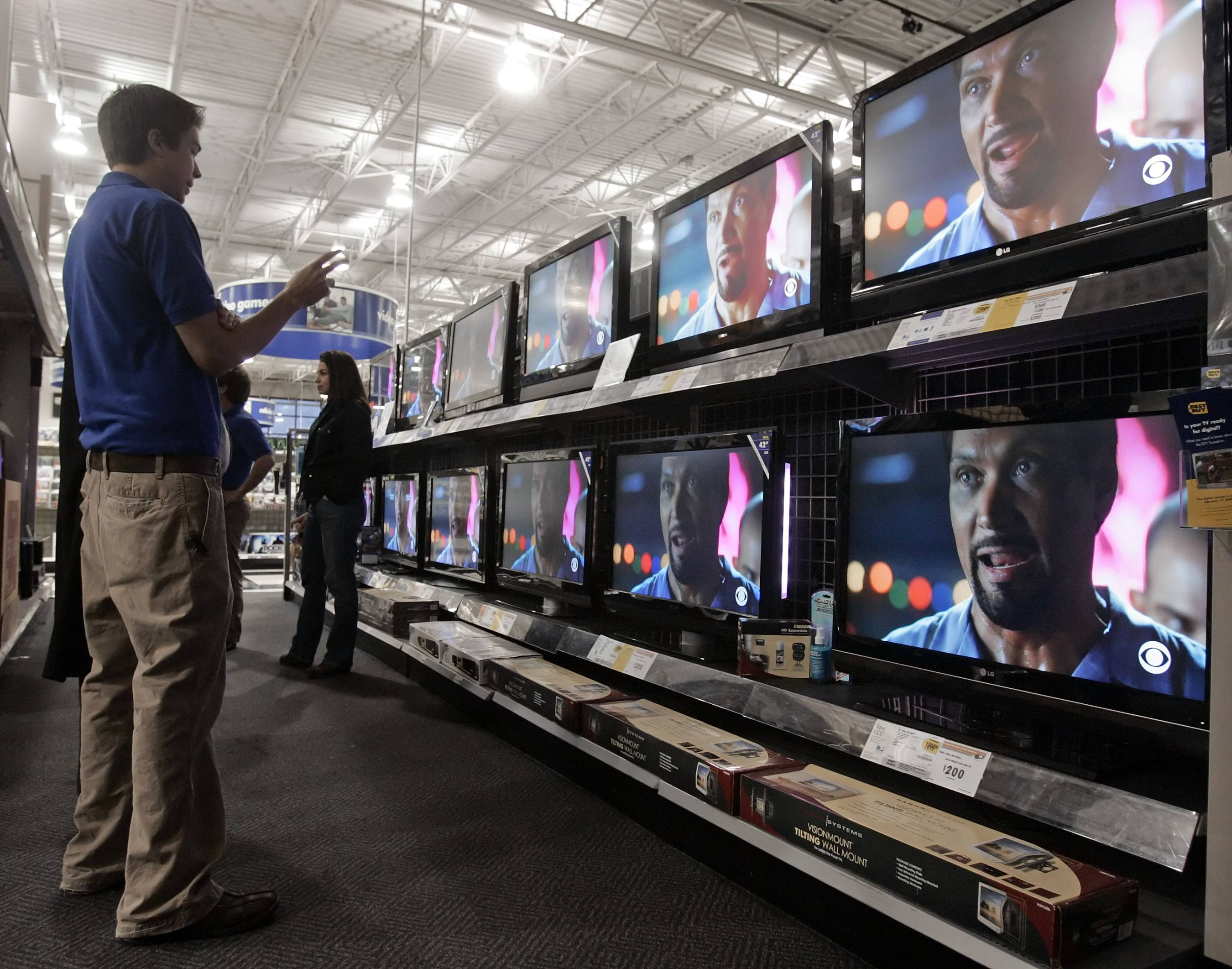 A salesperson helps a customer with information on big screen televisions at a Best Buy store in Nashville, Tenn. Offers of extended warranties or service contracts are becoming the norm, whether you buy a big-ticket item like a car or kitchen appliance or a less expensive one like a television or smartphone.